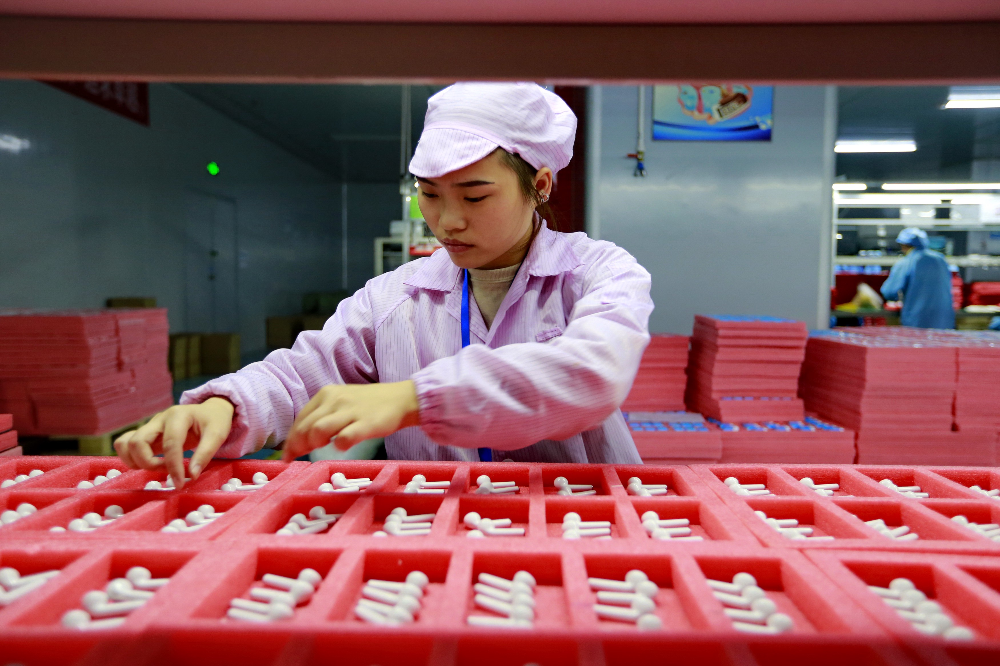 A woman worker assembles earphones for export in a factory in Suining in southwest China's Sichuan province on Dec. 17, 2019.