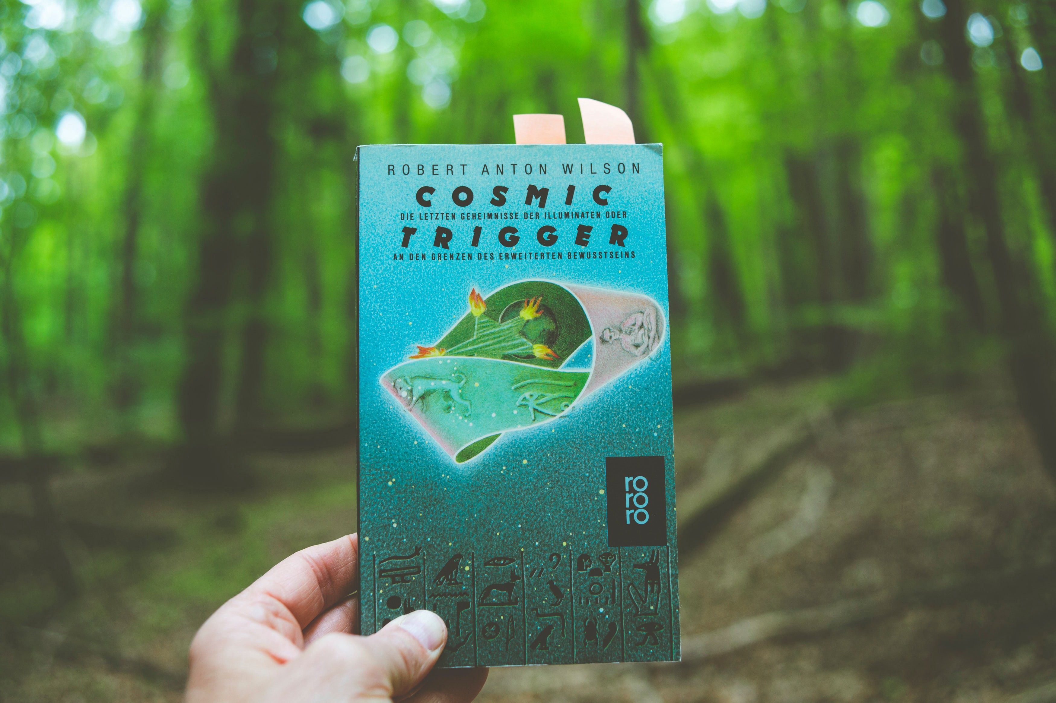 Photo by Markus Spiske on Unsplash, another book held up in the forest. Cosmic trigger