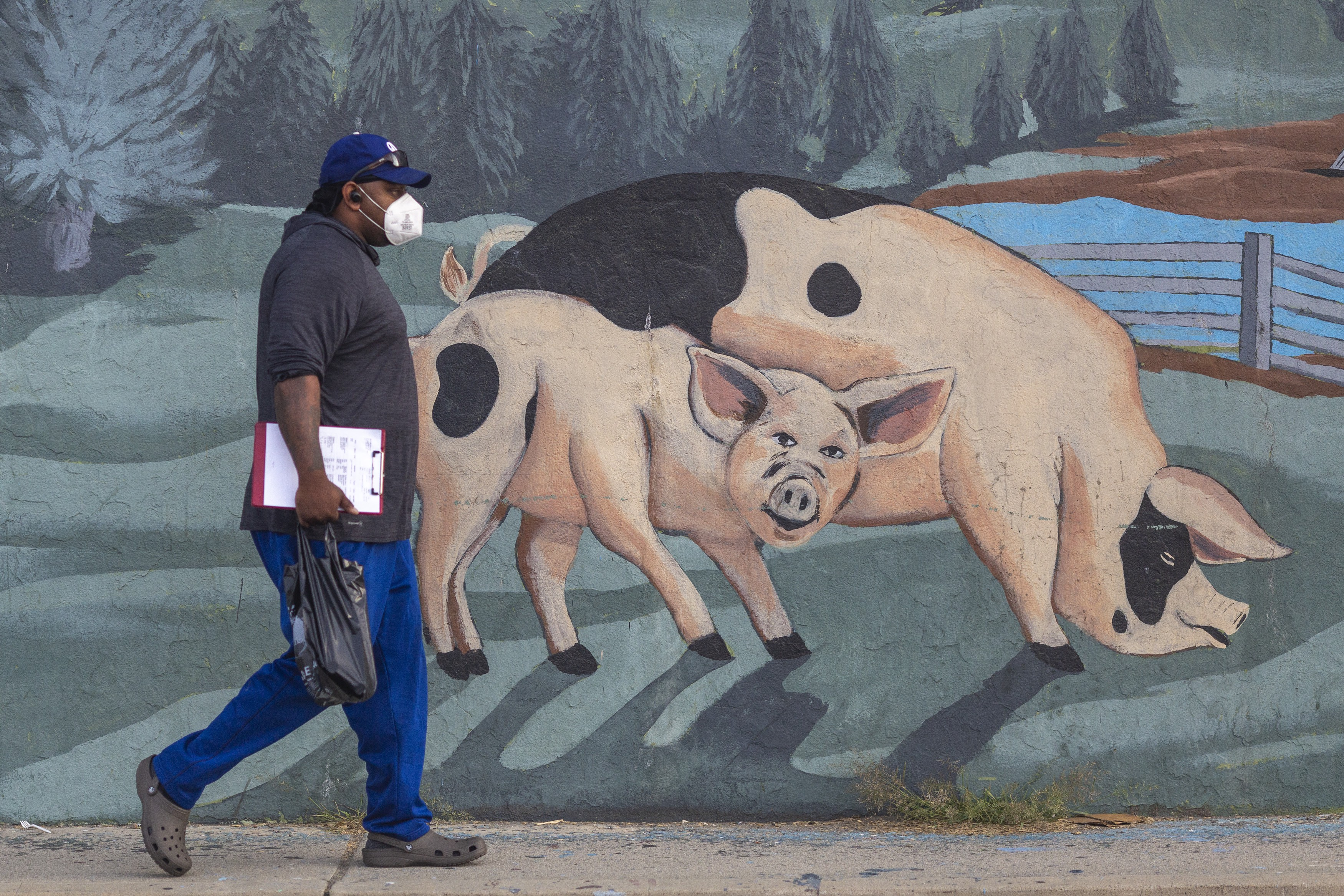 A man walks past a mural on the Farmer John slaughterhouse in Vernon, CA after 153 workers tested positive for Covid-19