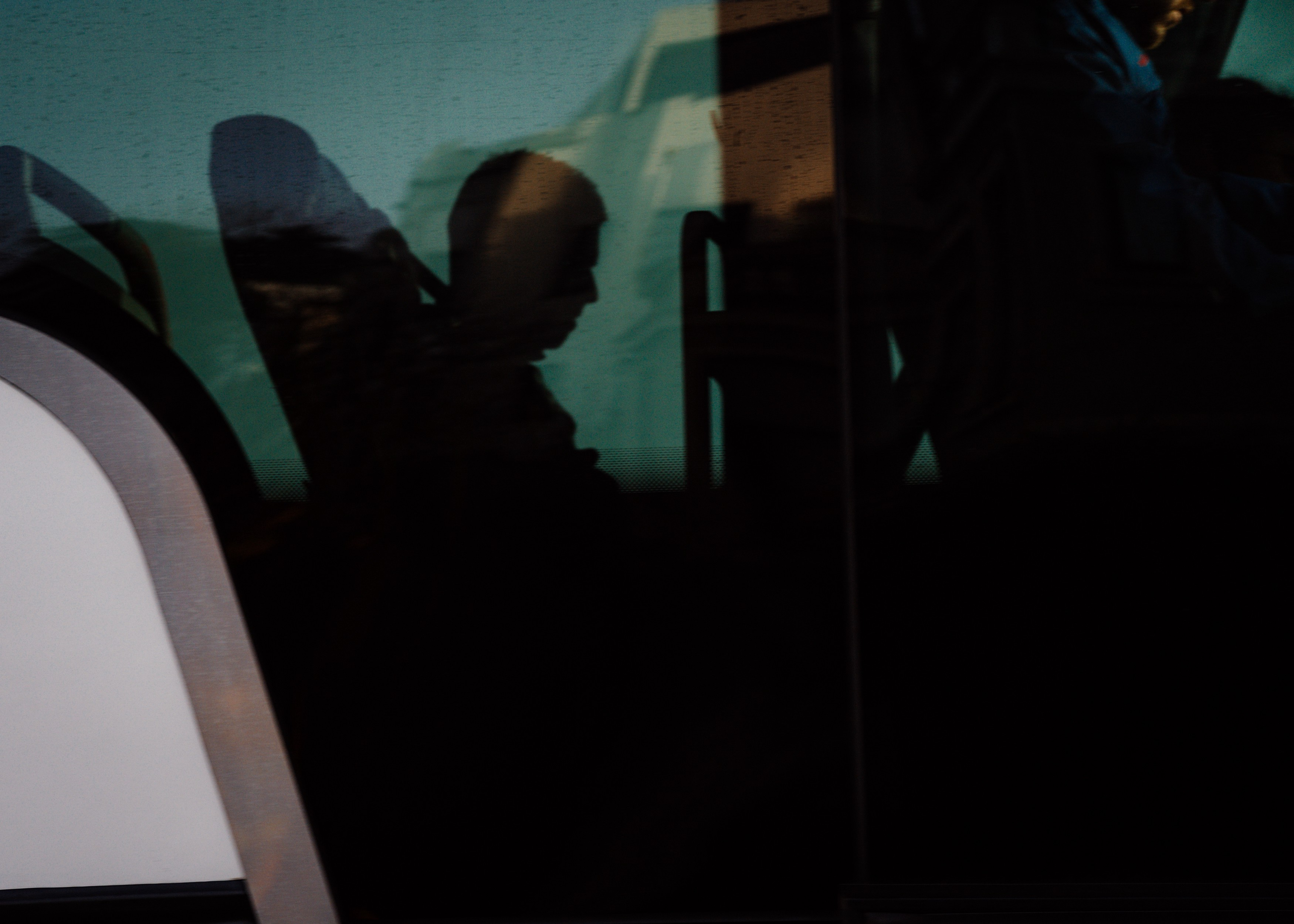 A silhouette of a tech worker sitting on the shuttle bus going to a tech campuses in and around Silicon Valley.