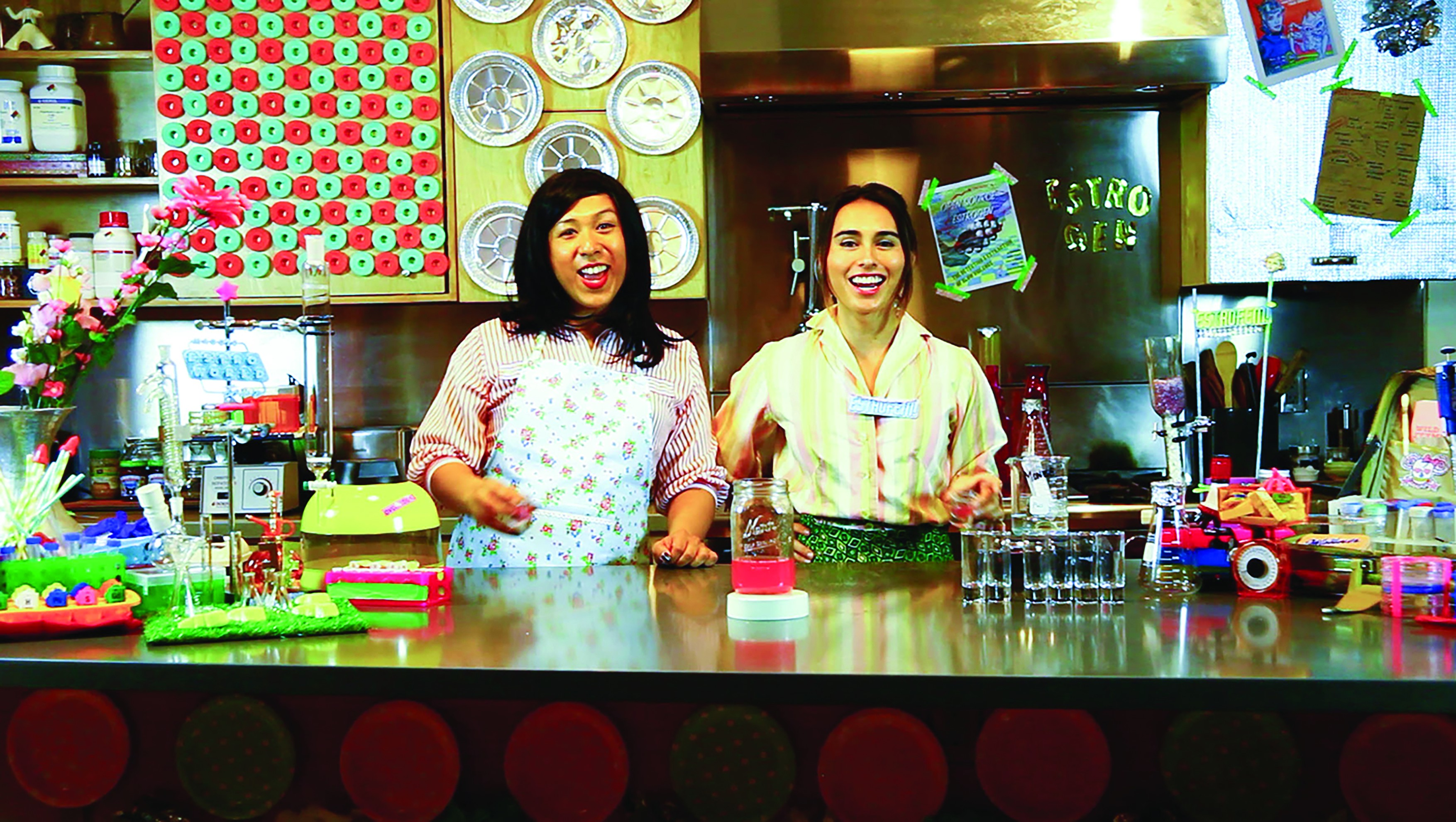 Two television hosts stand in bright and colorful kitchen with science lab kit making homemade estrogen hormones
