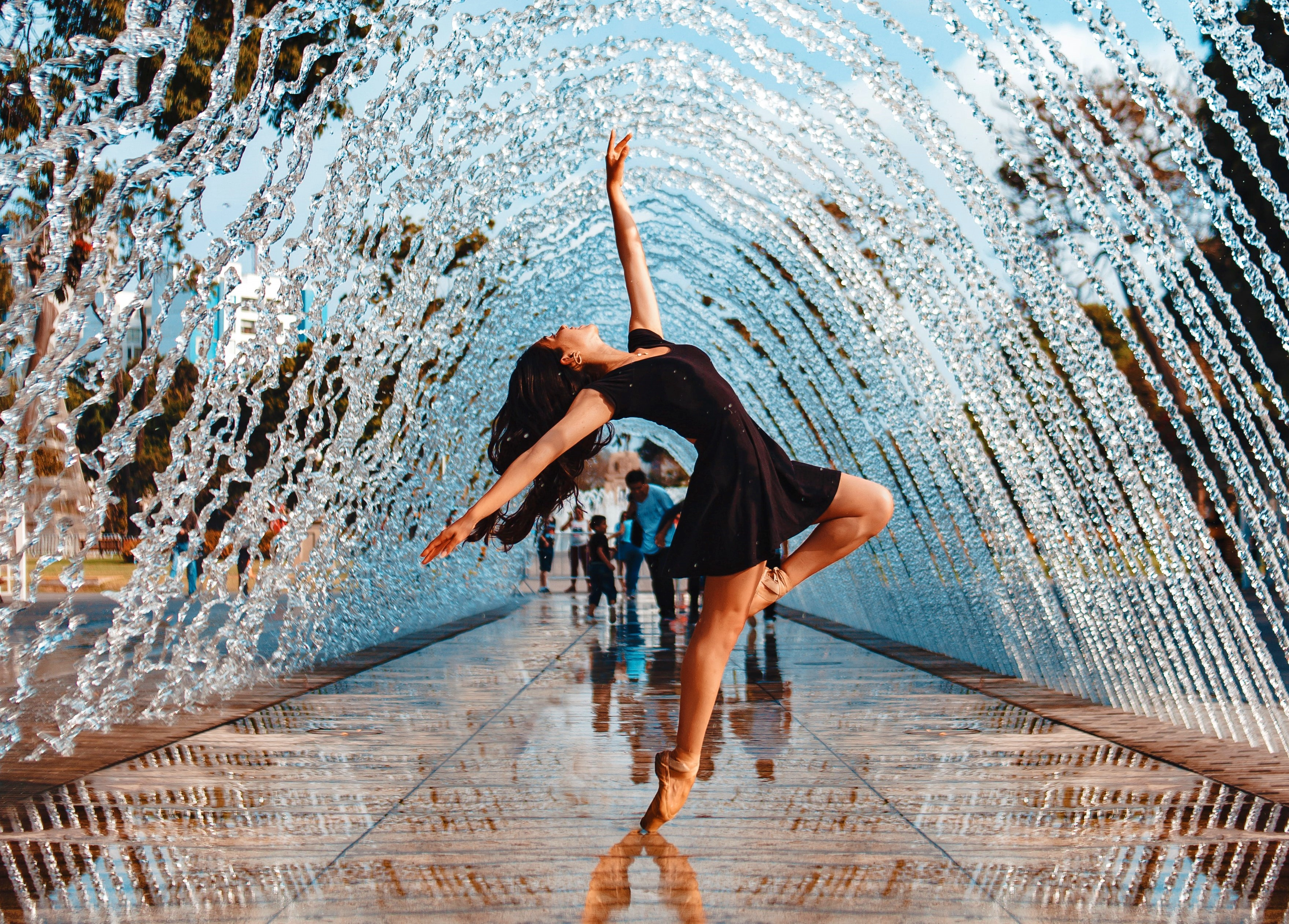 female dancer with dark hair wearing black dress in outstretched pose under water fountain
