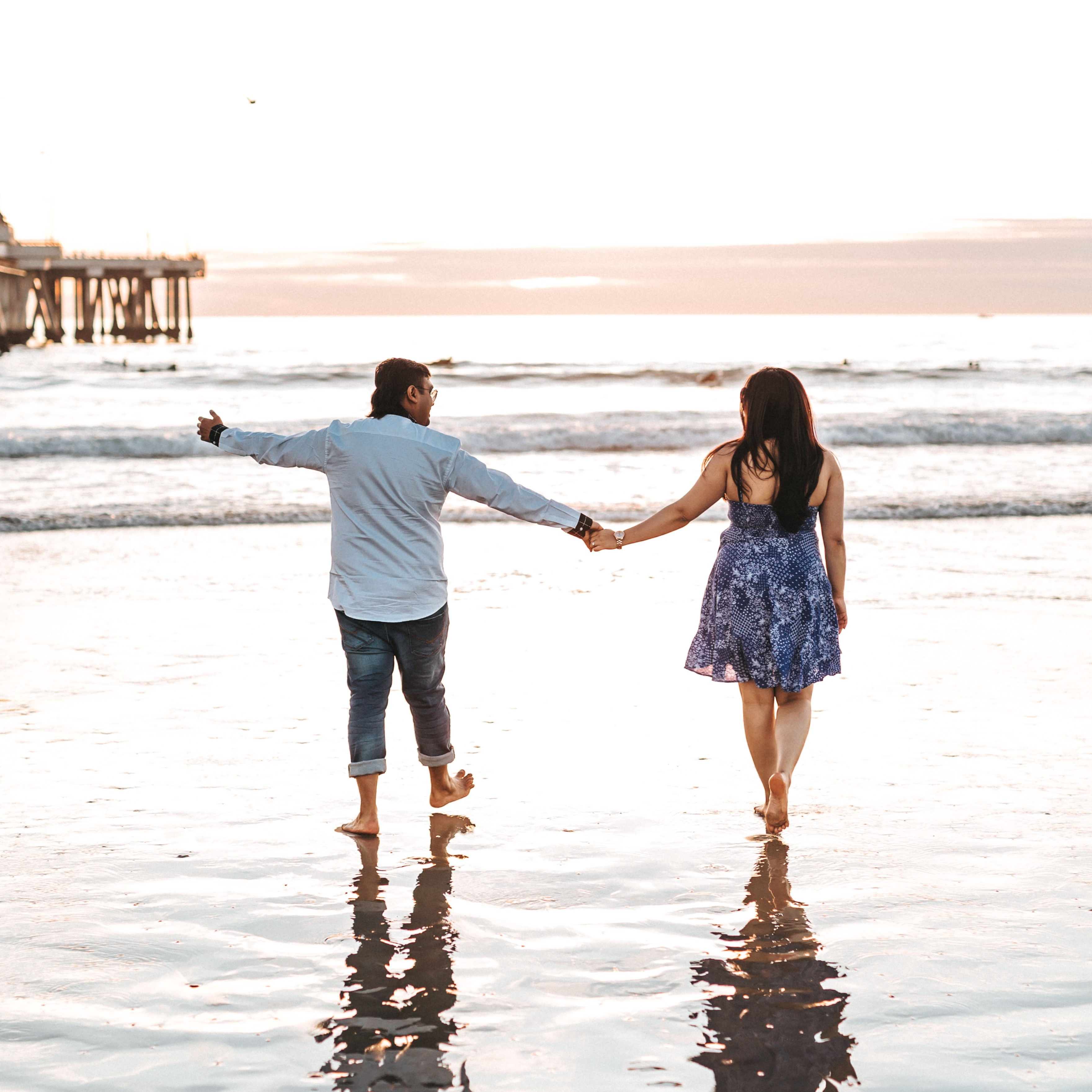 A man and a woman walk along a beach, holding hands. The man has one arm outstretched, as if gesturing at something.