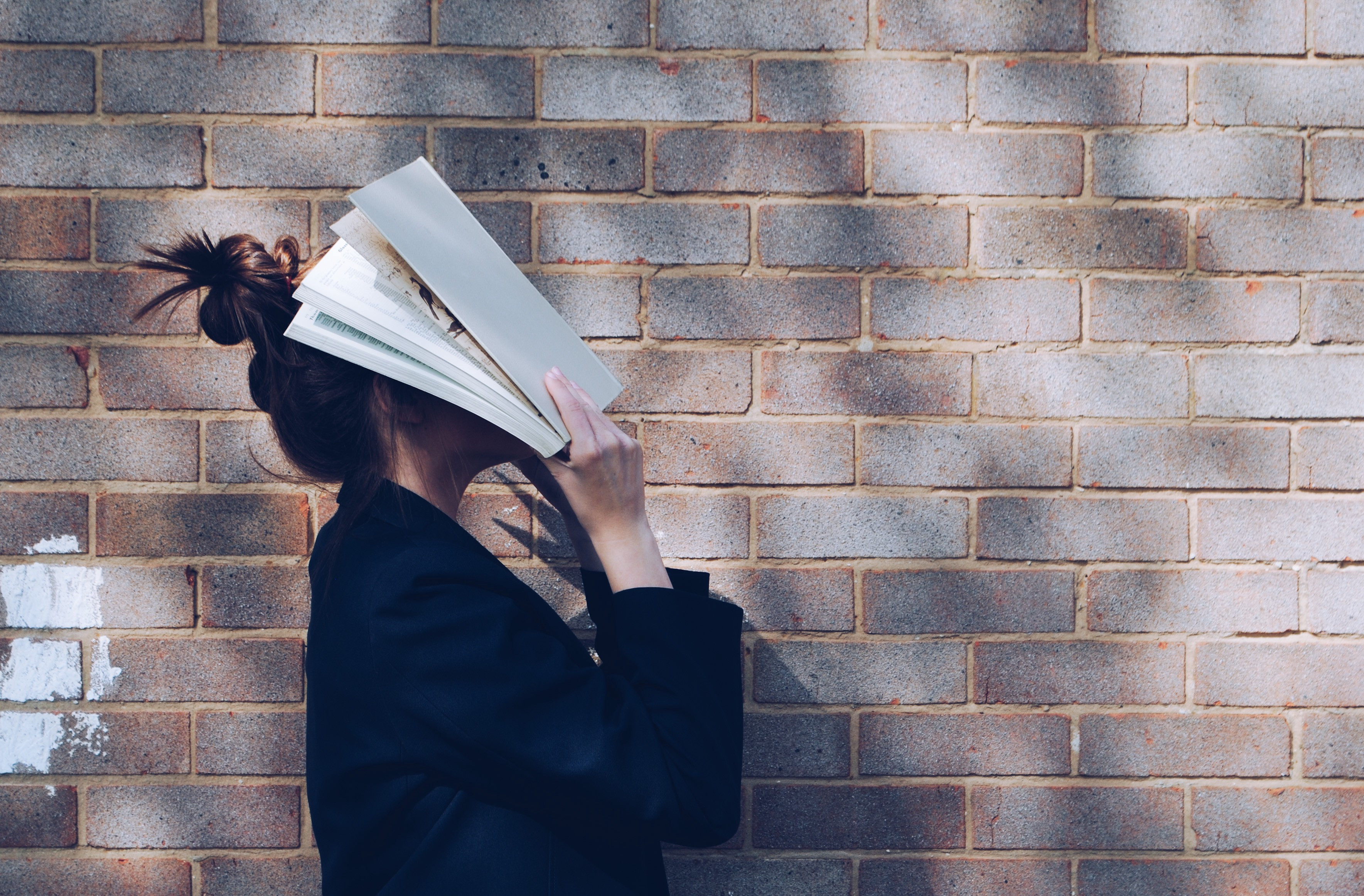 Girl stood next to a brick wall, holding a book over her face.