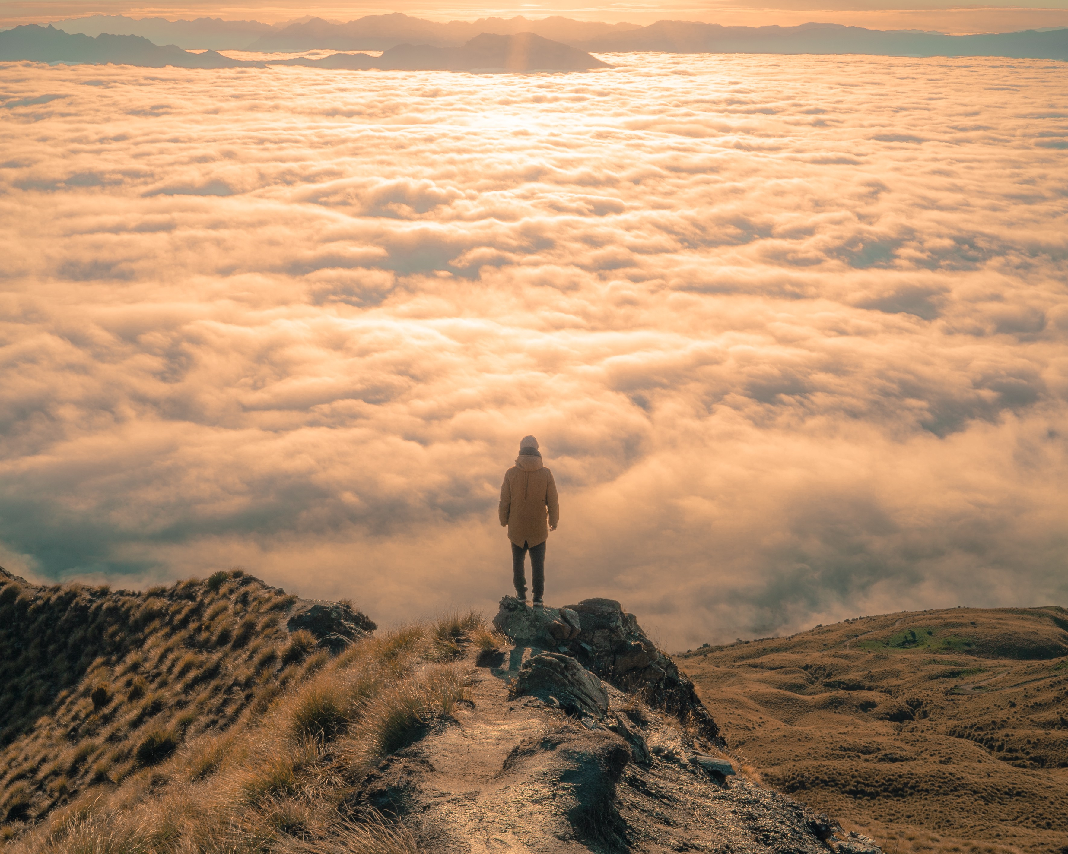 A man standing up on a mountain top, gazing out into the clouds