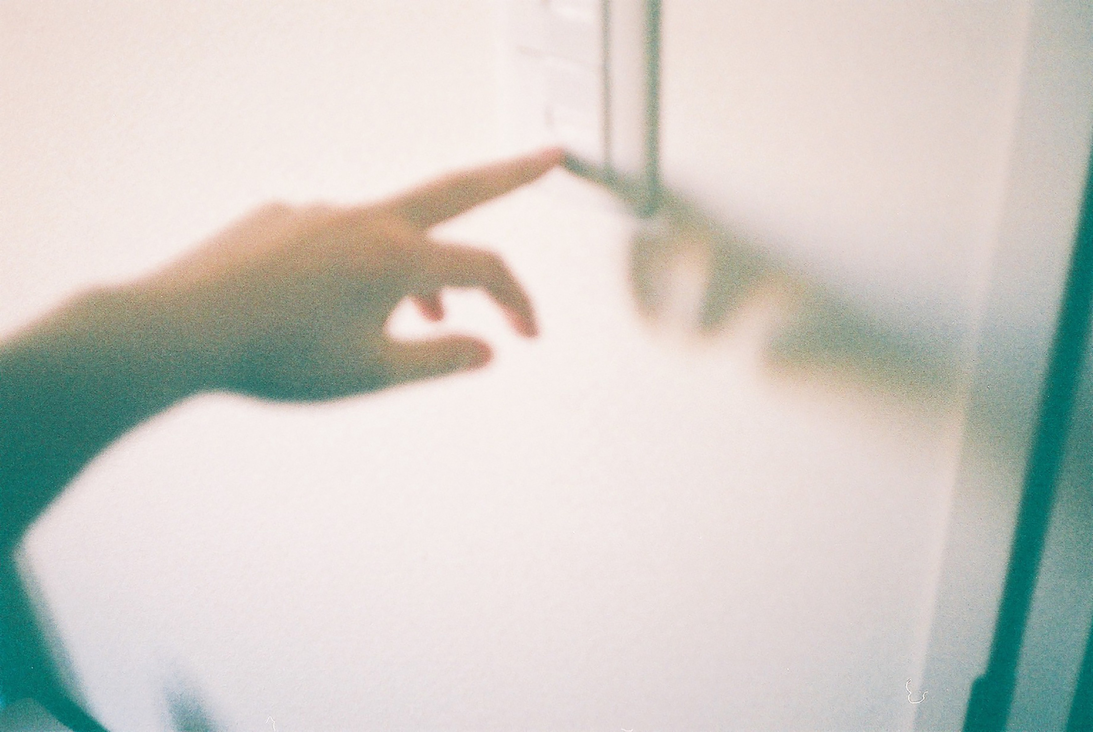 A washed out grainy image of a person touching a light switch.