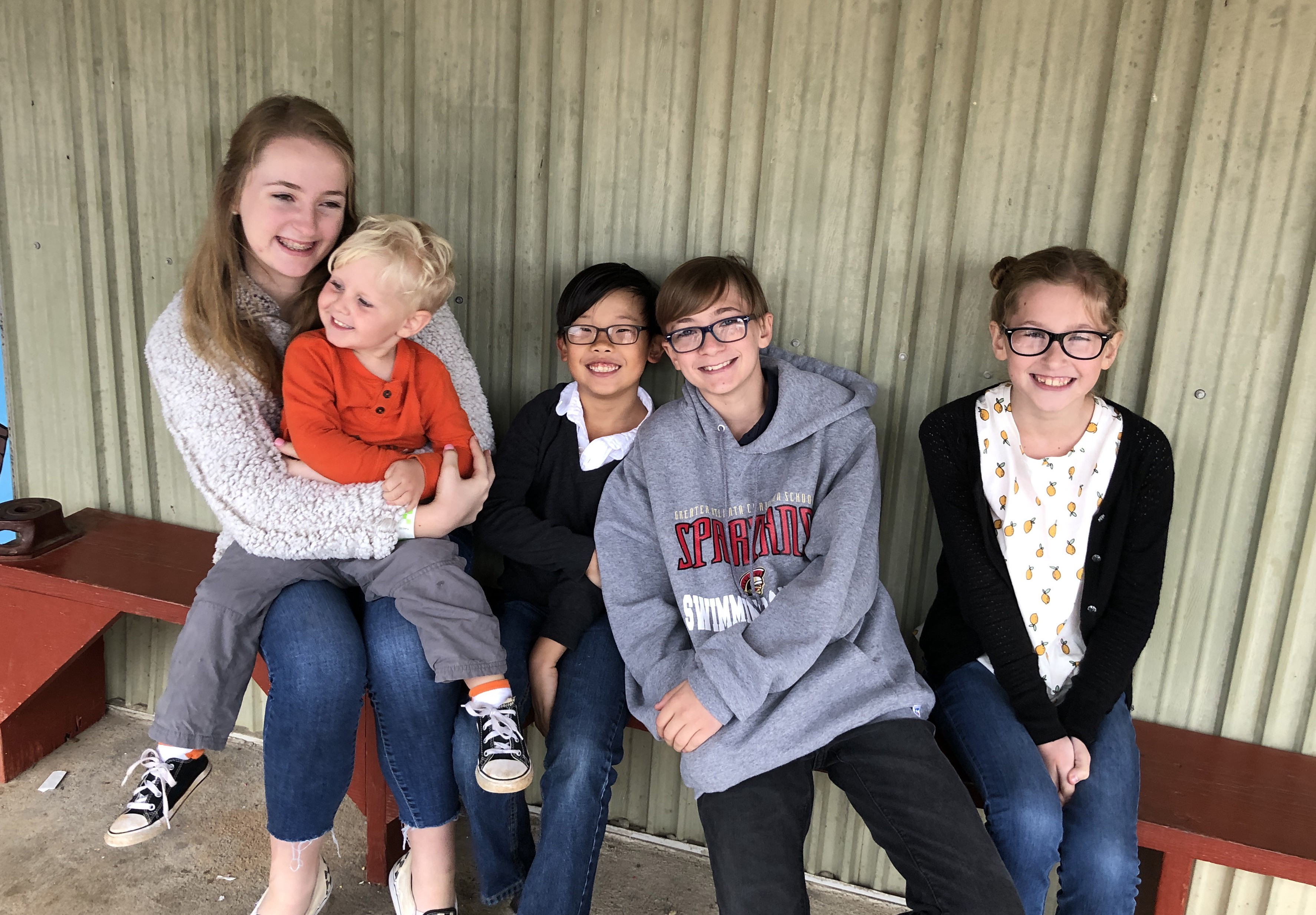 Our five kids sitting and smiling at the camera.