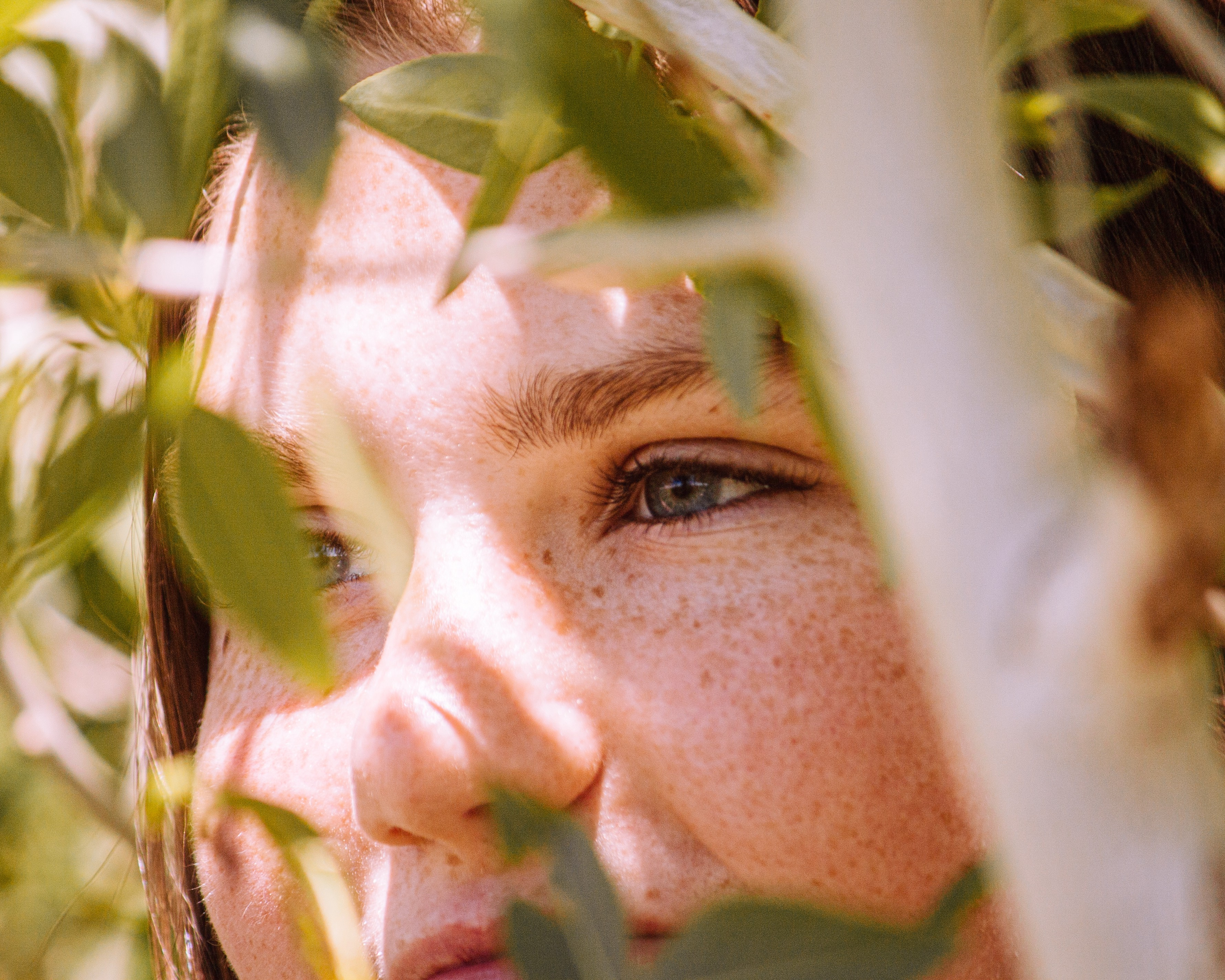 Photo of a girl in between leaves on a hot day.