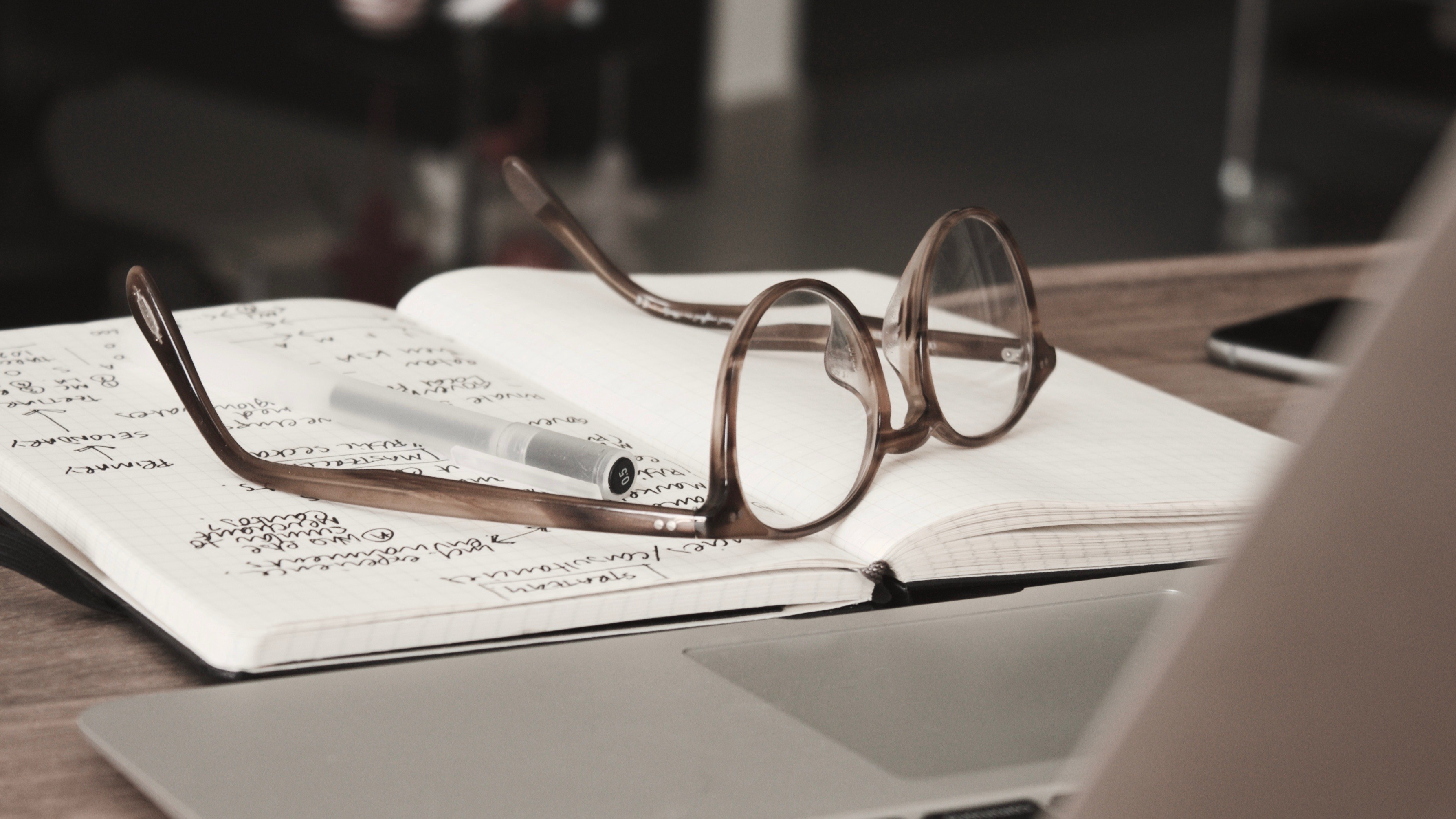 Photo of a small notebook with glasses and a pen rested on top of its open pages. There is an open laptop in front of it.
