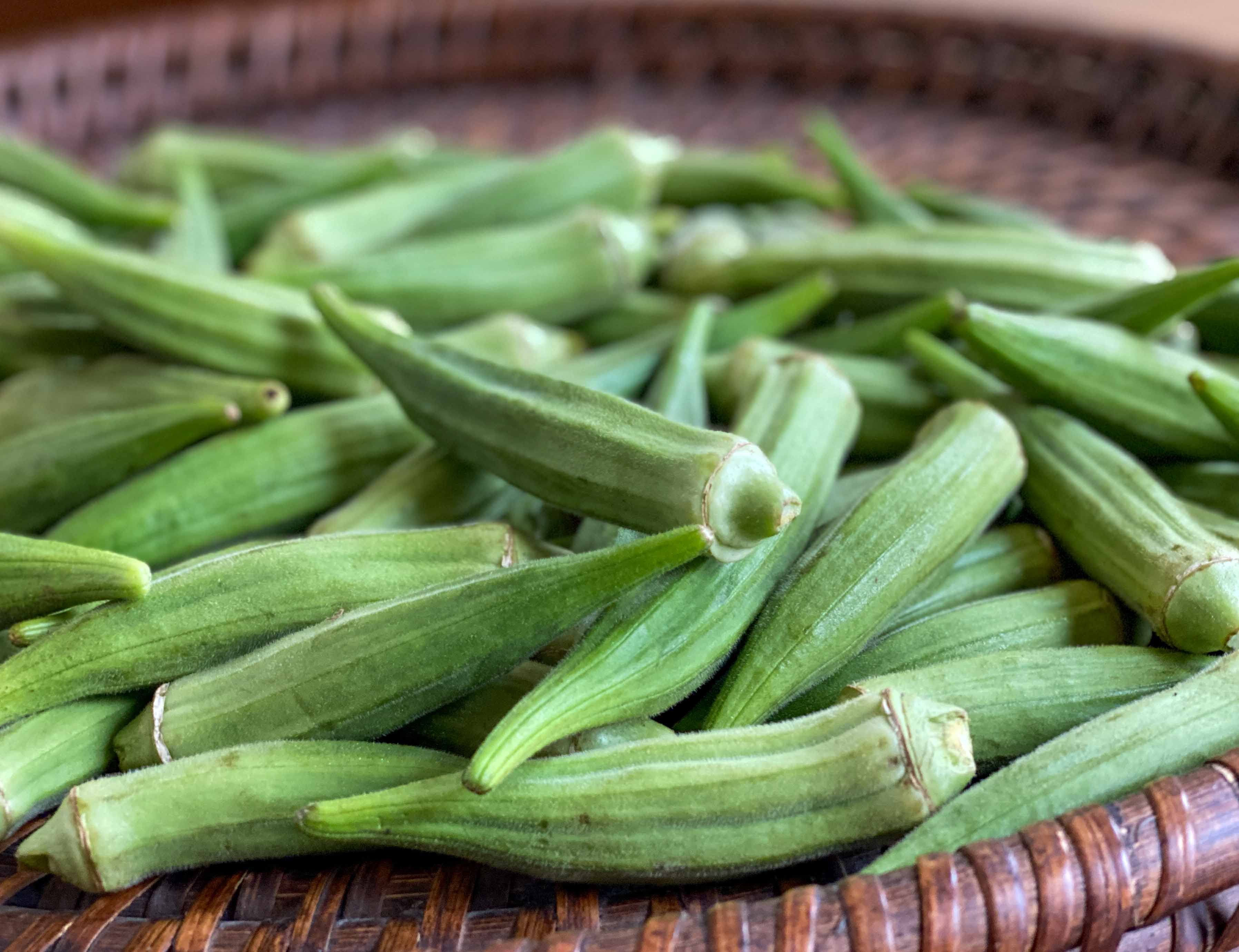 Fresh okra pods are spread on a brown basket.