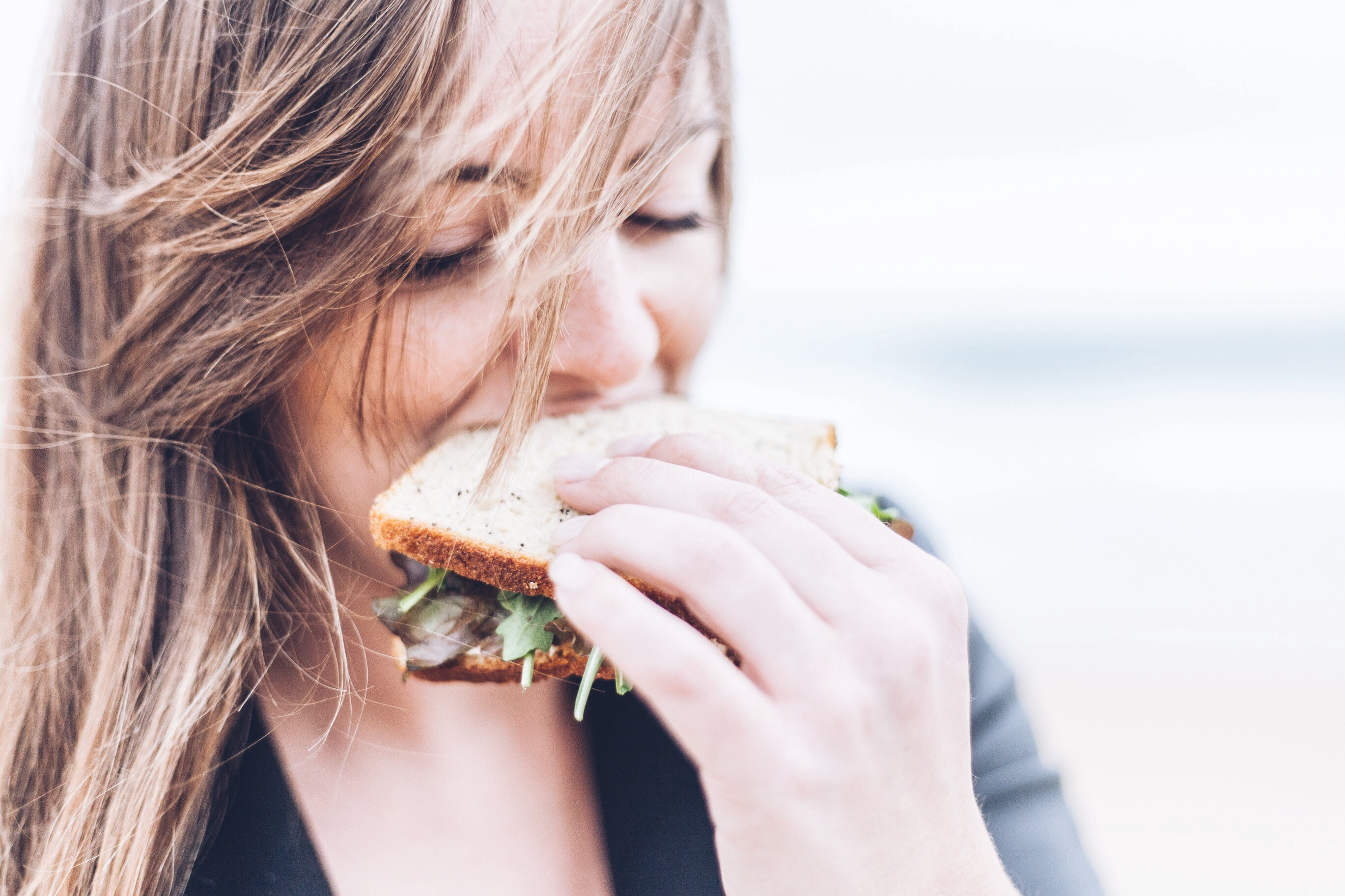 Woman on diet eating a boring sandwich