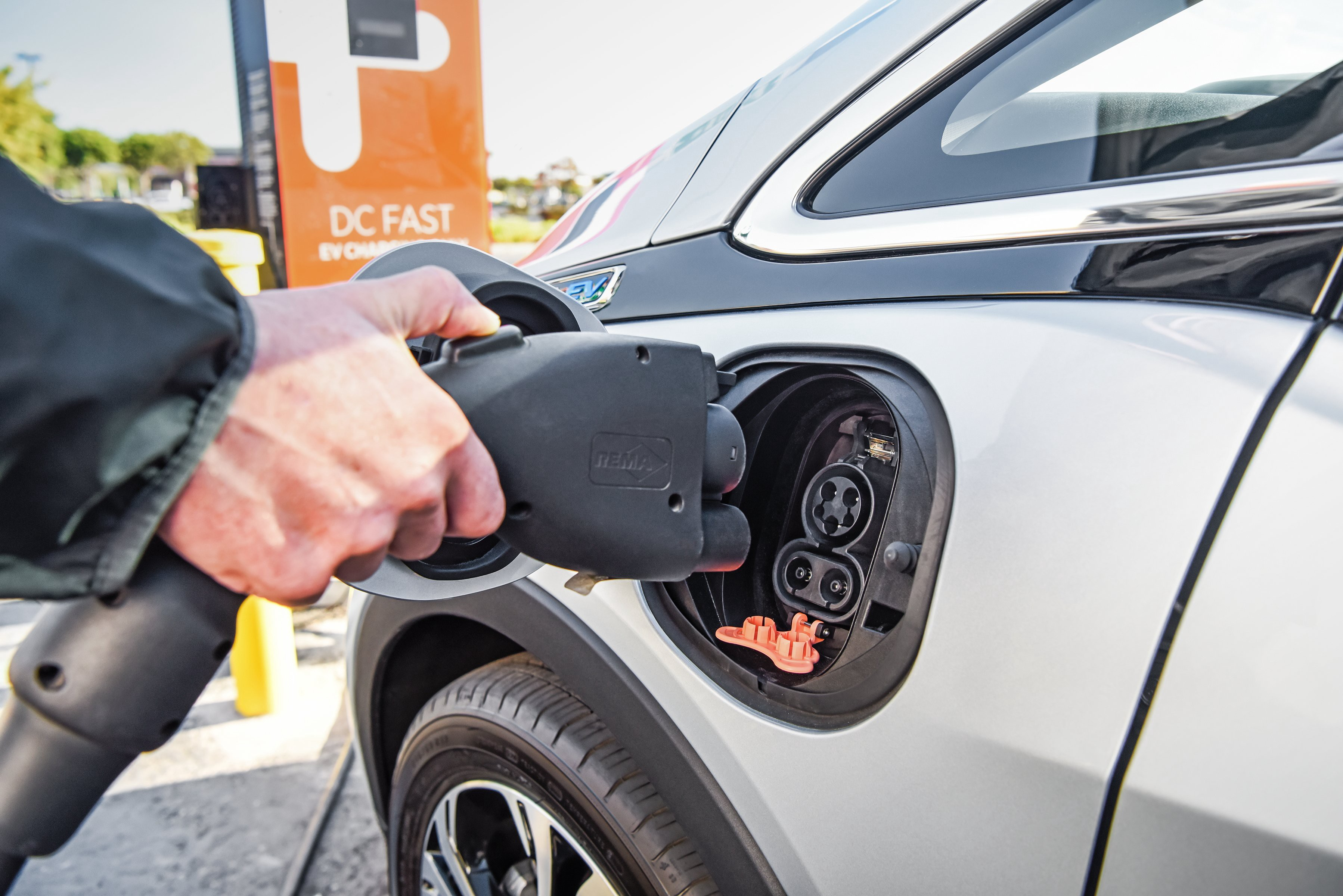 A hand plugging an electric car in to charge.