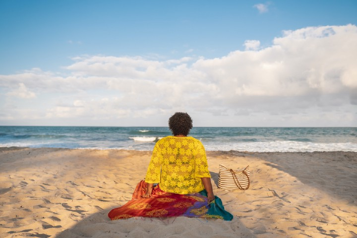 Rear view of a fat Black woman sitting on a towel on the beach, watching the ocean.