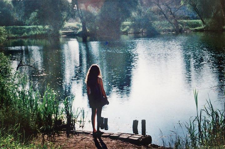 A photo of the back of a woman standing in front of a lake.