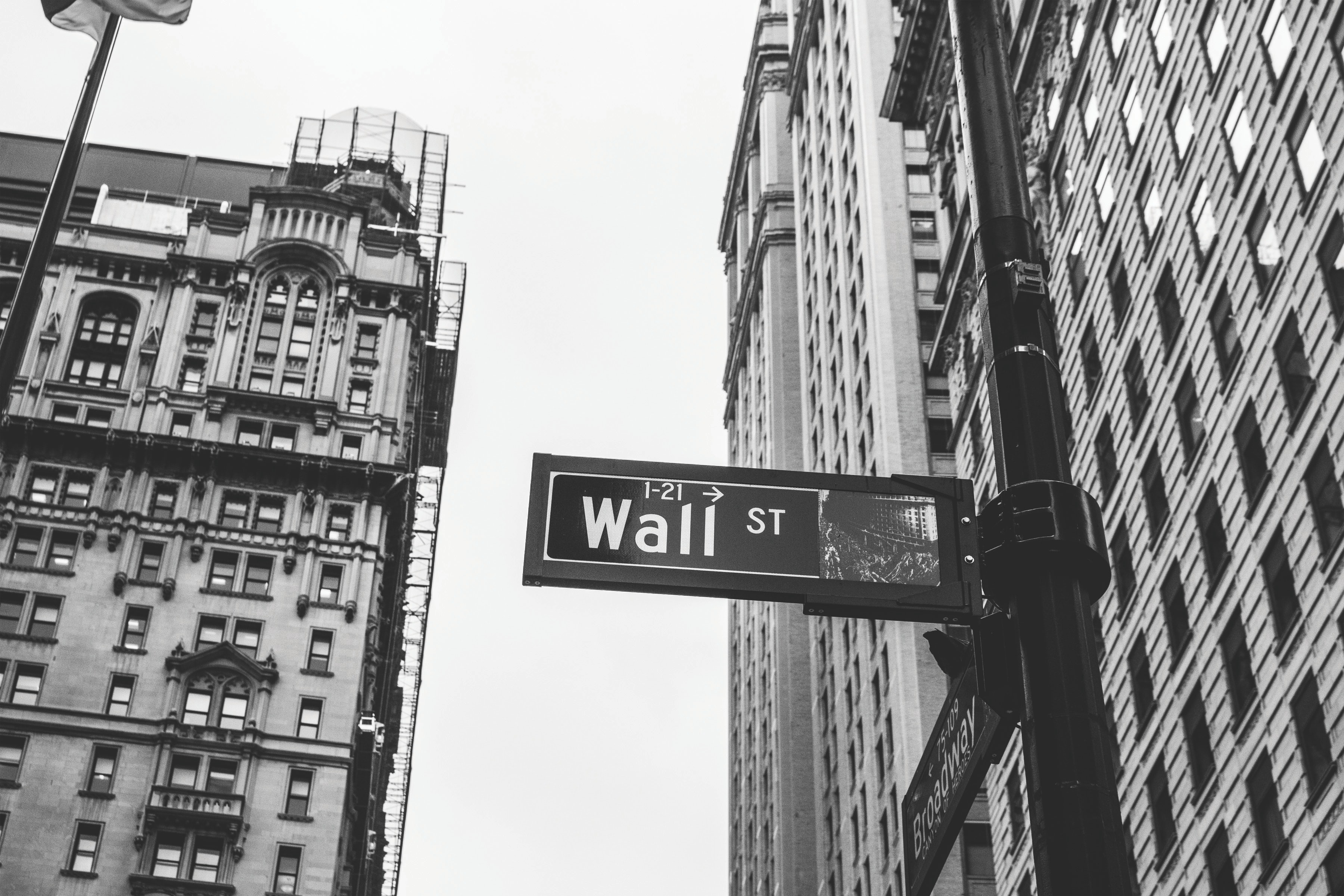 Black and White photo of downtown New York, Wall Street and Broadway street sign.