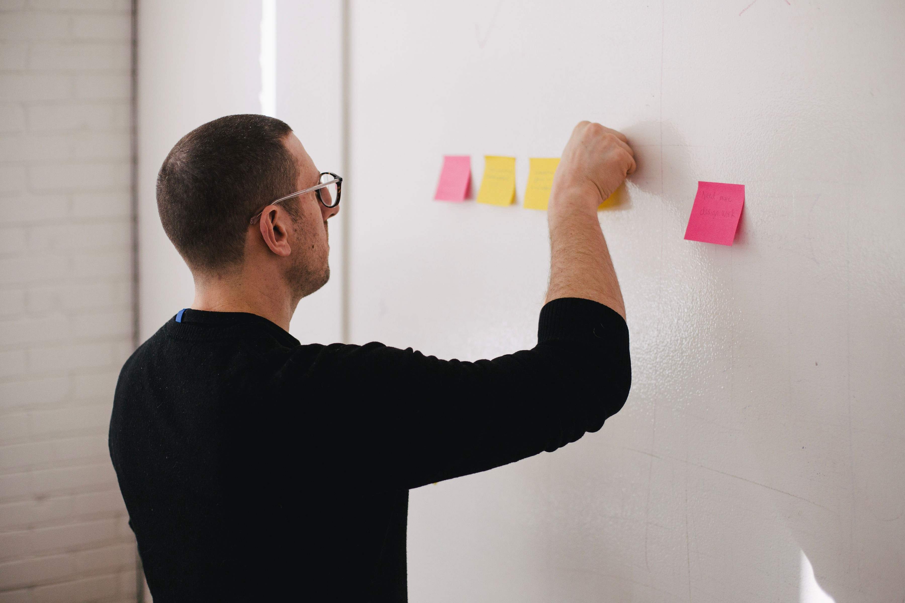Person placing sticky notes on a board