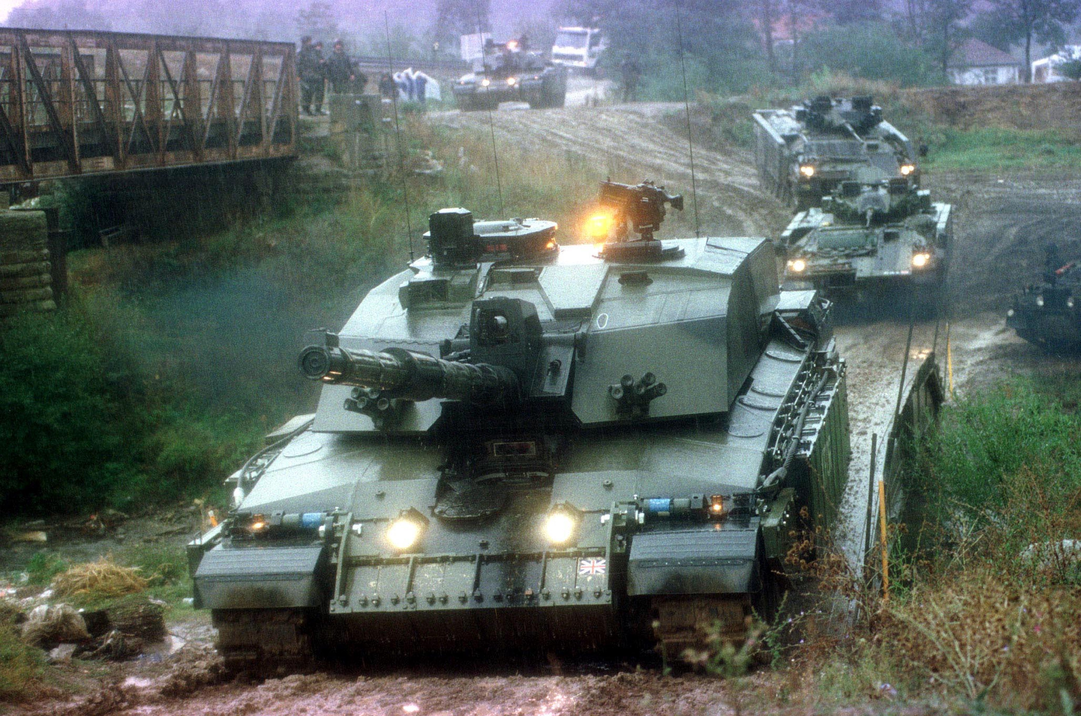 A Challenger 2 main battle tank leads Warrior Infantry Fighting vehicles over a bridge during battle group manoeuvers in Kosovo (1999).