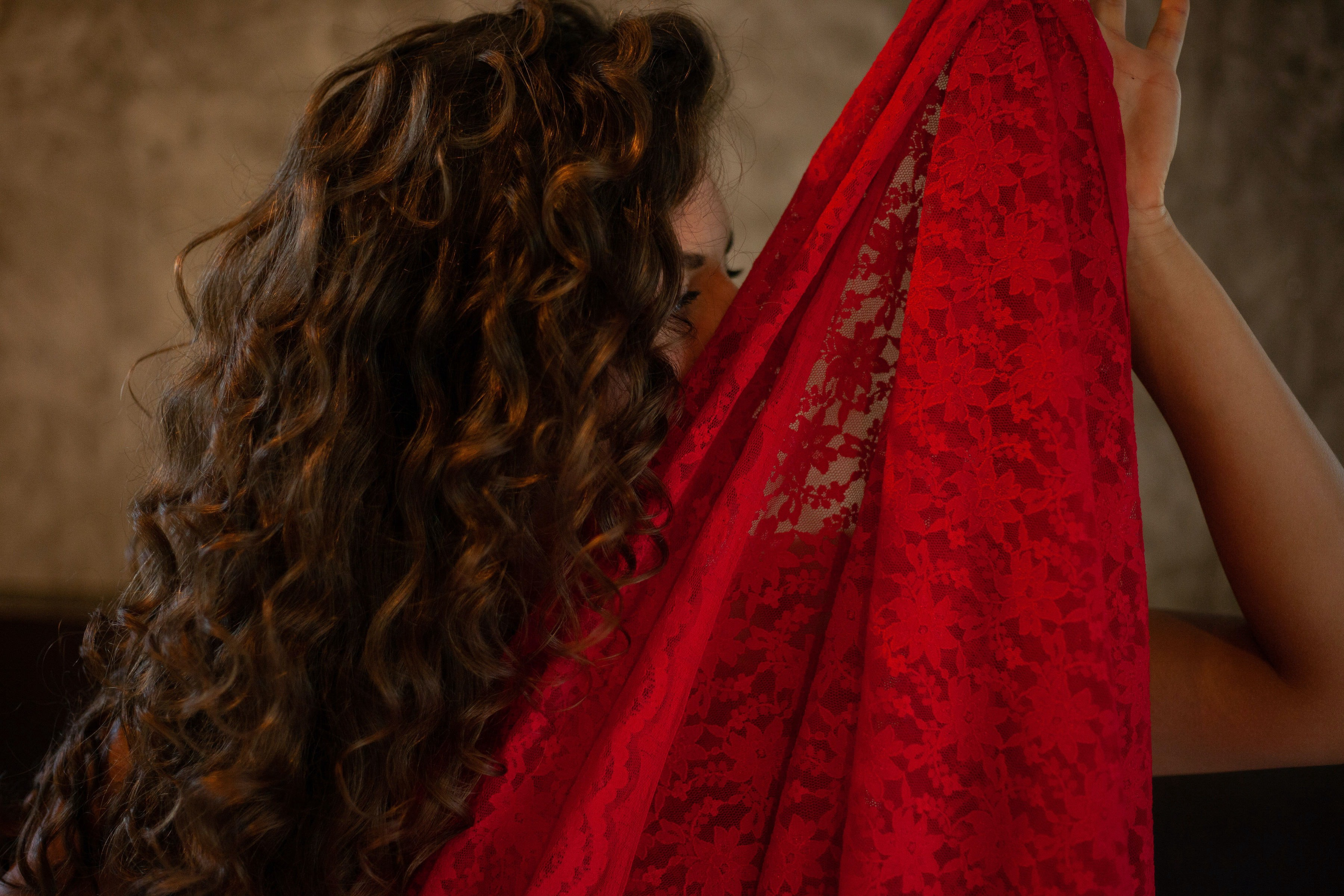 sensual woman holding up a red lace veil