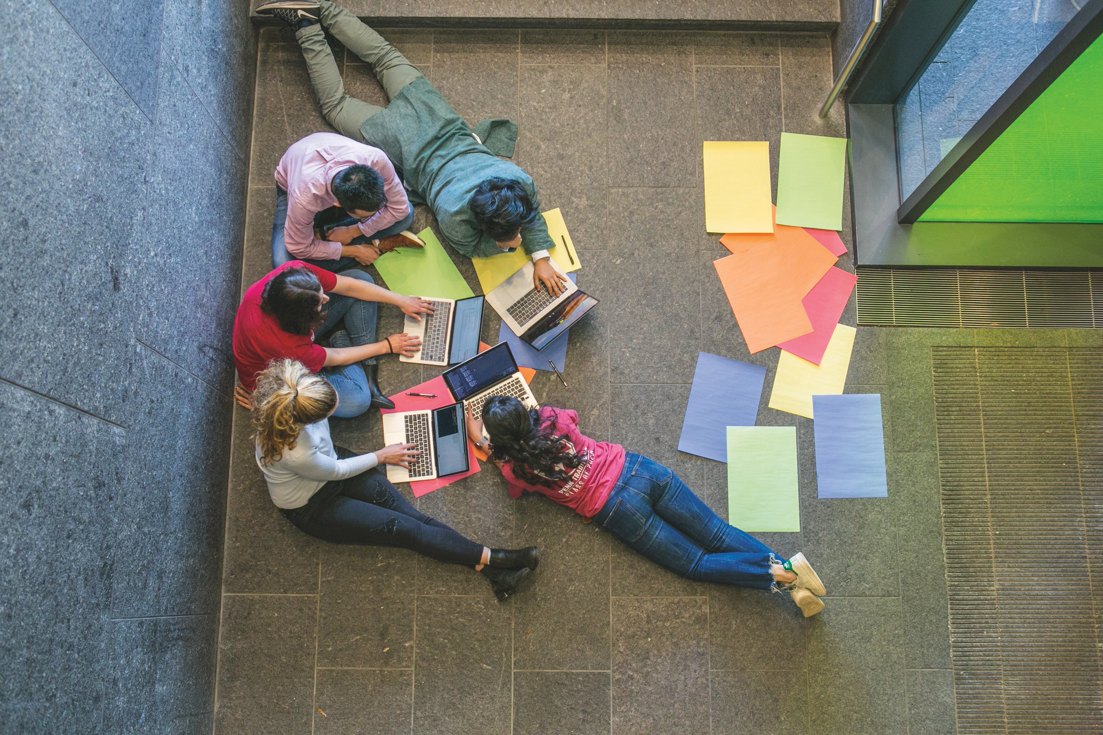 Students sit on the floor in lobby of Skirkanich Hall, working with laptops and construction paper.