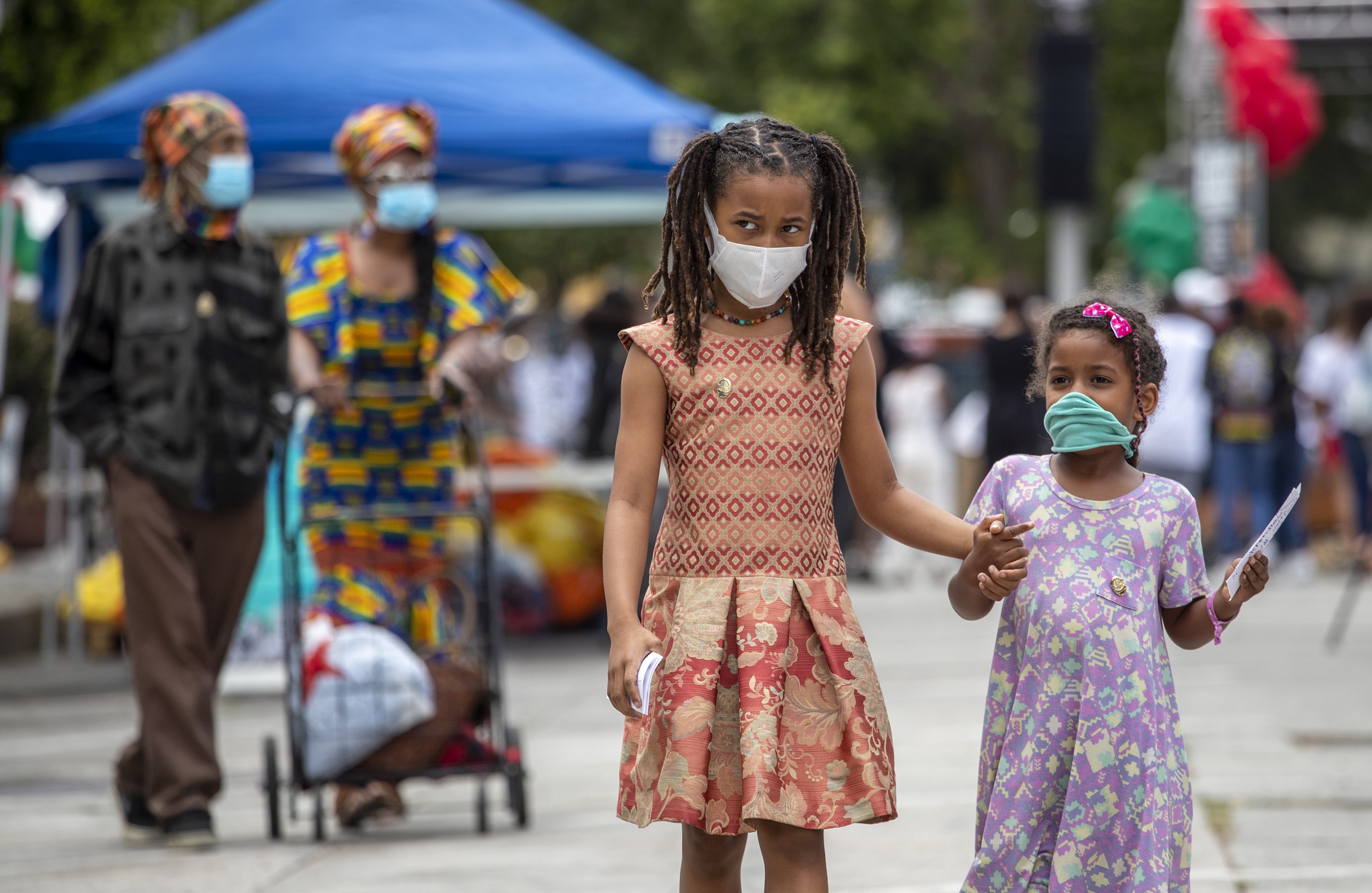 Two young African-American girls walk together, holding hands during the Leimert Park Rising Juneteenth celebration in LA.