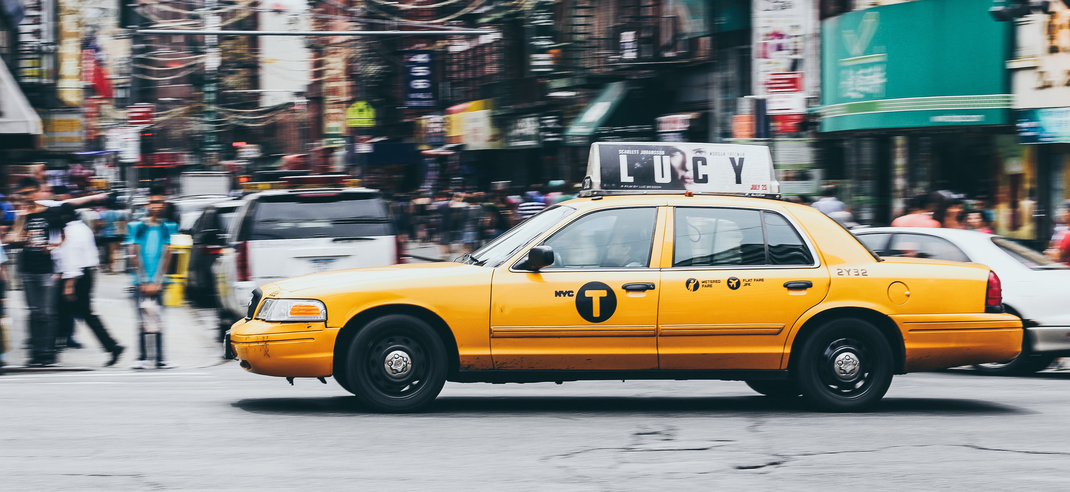 A New York taxi races across an intersection.