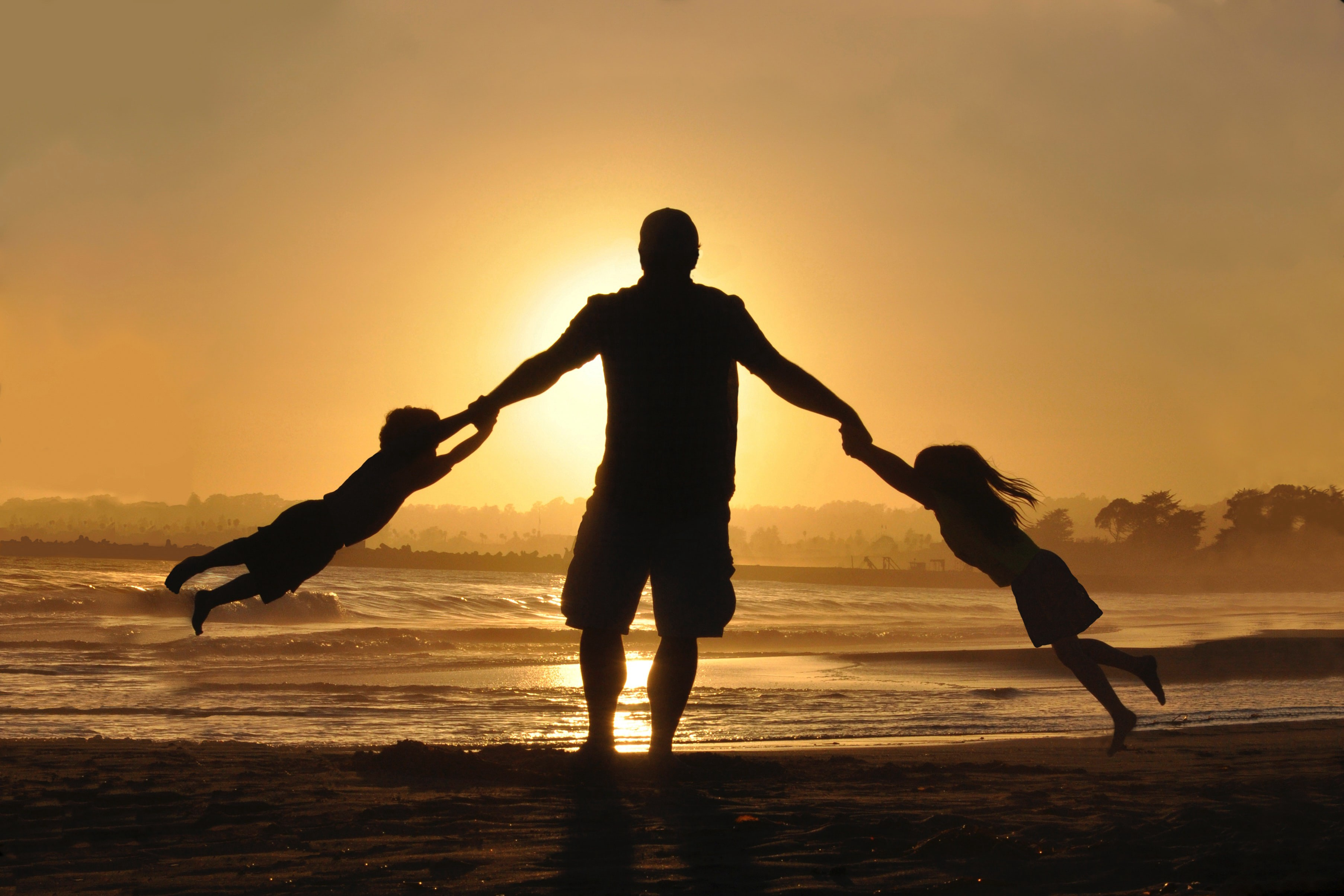 An adult swinging kids from their arms at the ocean during sunset. Symbolizing present parenting and play.