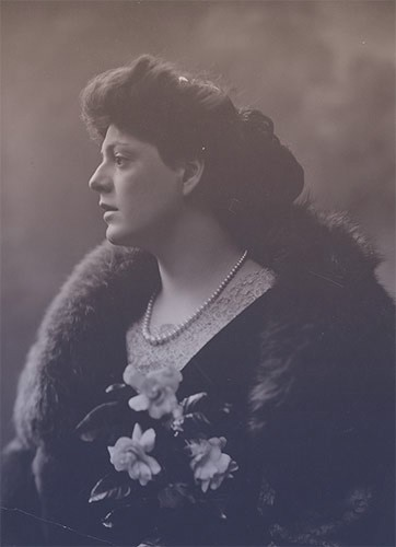 Ethel Barrymore in profile, wearing a dark dress, fur coat, and a single strand of pearls.