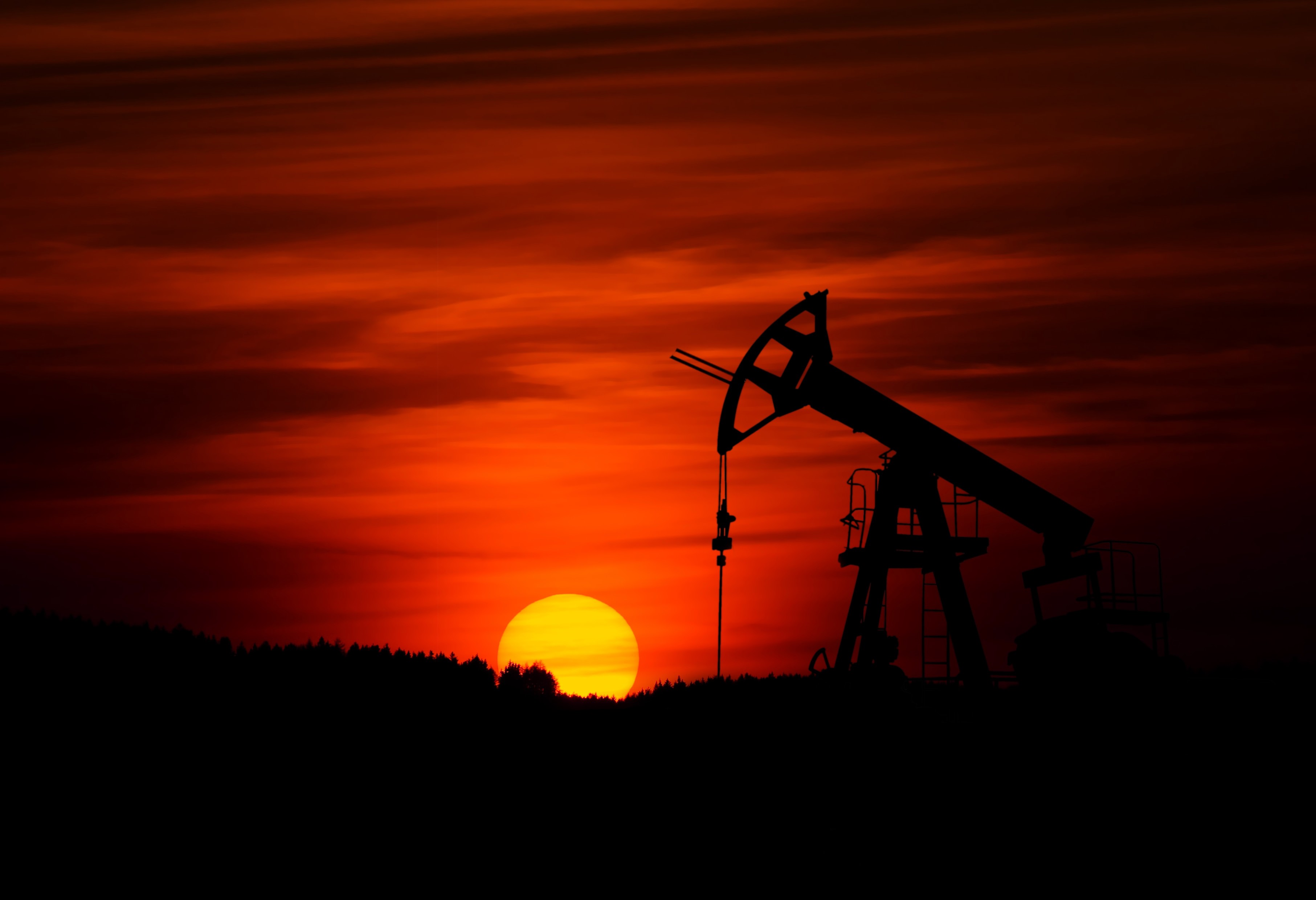 Oil field at sunset. An dark oil machine sits in the dark foreground against a red, orange sky. The sun is yellow.