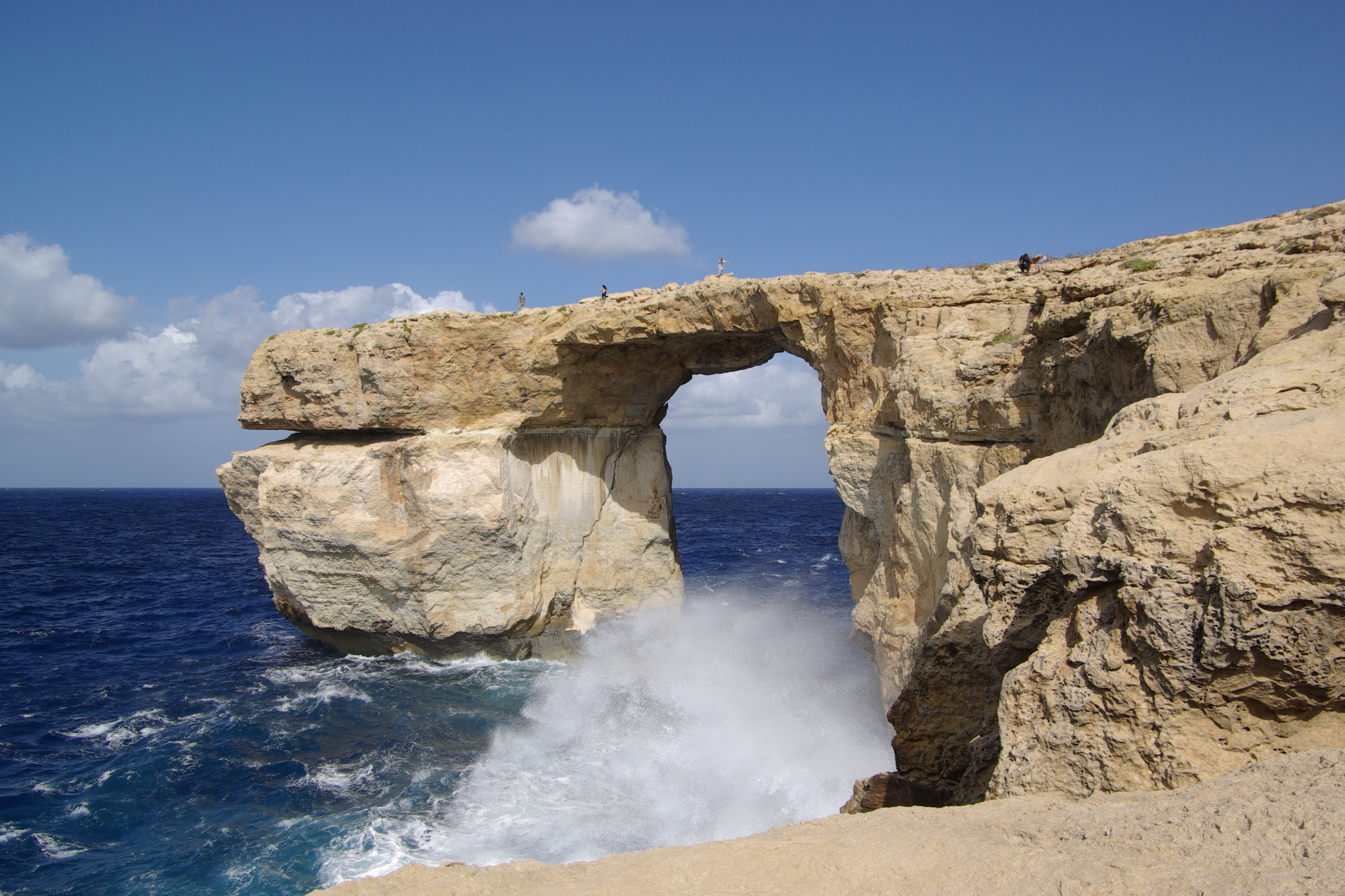 The image shows a rock feature called the Azure Window in Gozo, Malta, as waves crash against the coast.