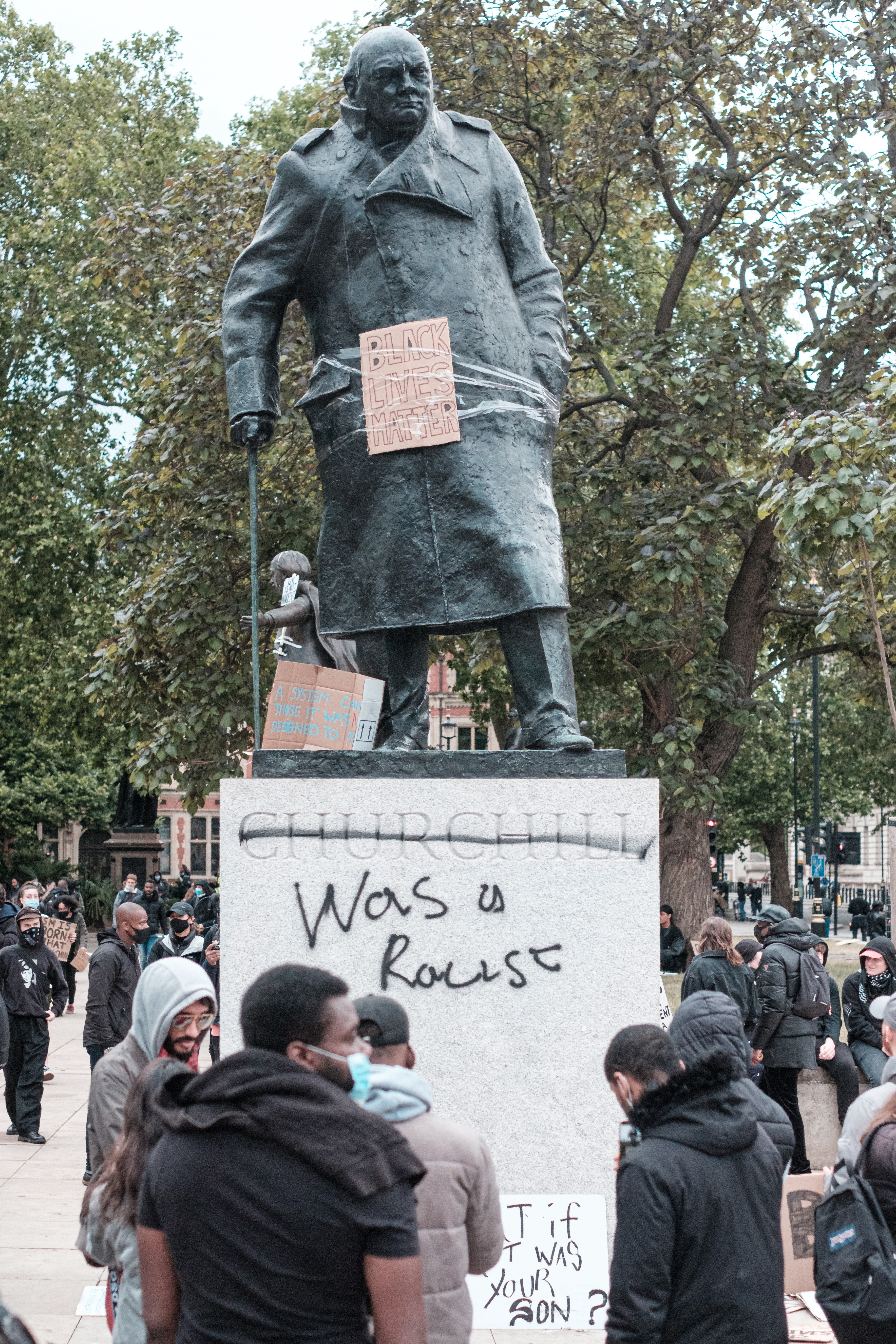 """An image of a group of people in protest against a Winston Churchill statue that has been spray painted with words to read """"Churchill was a racist"""". The statue holds up a sign that reads """"Black Lives Matter"""""""