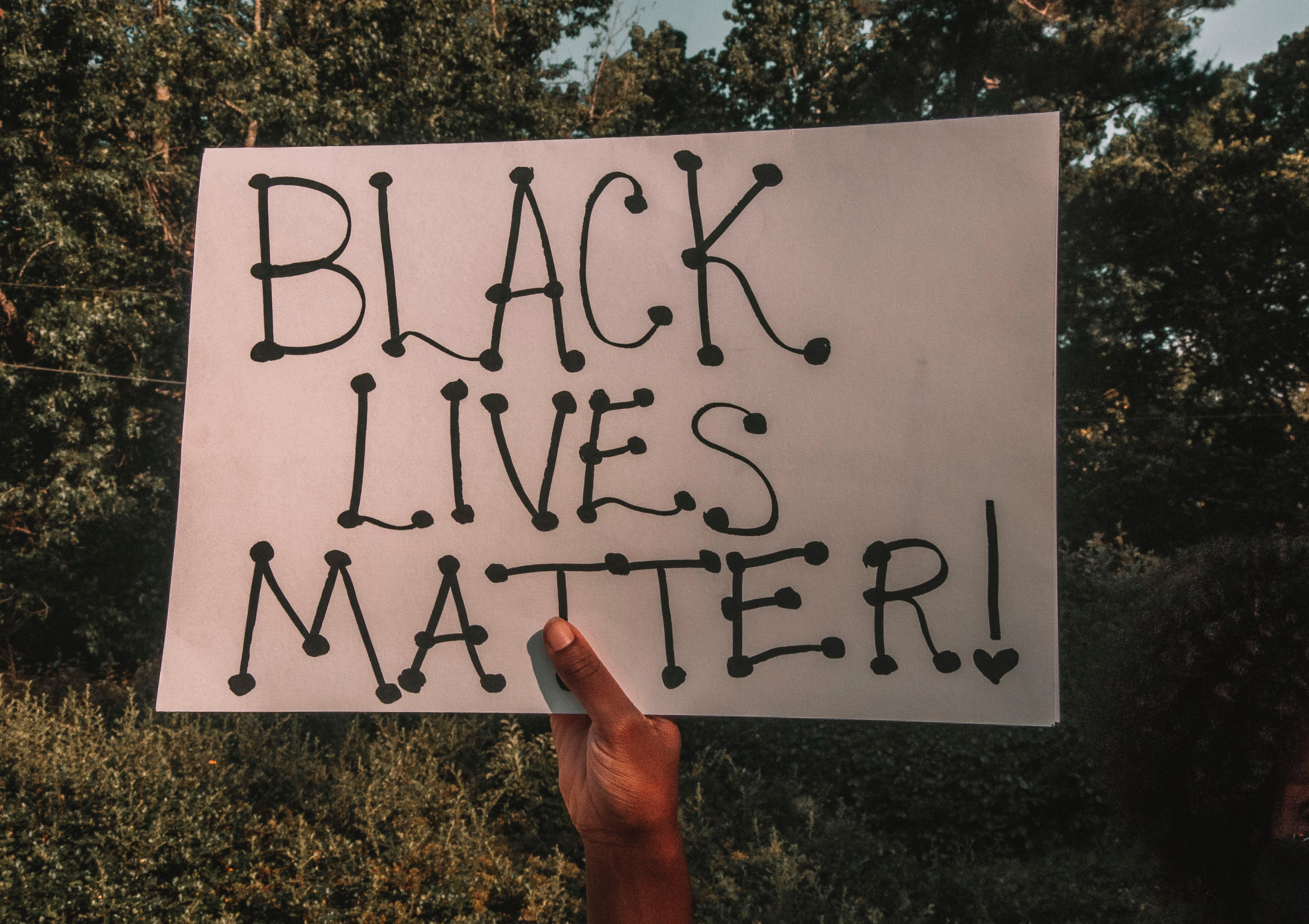 """A black hand holds up a sign that reads """"Black Lives Matter!"""""""