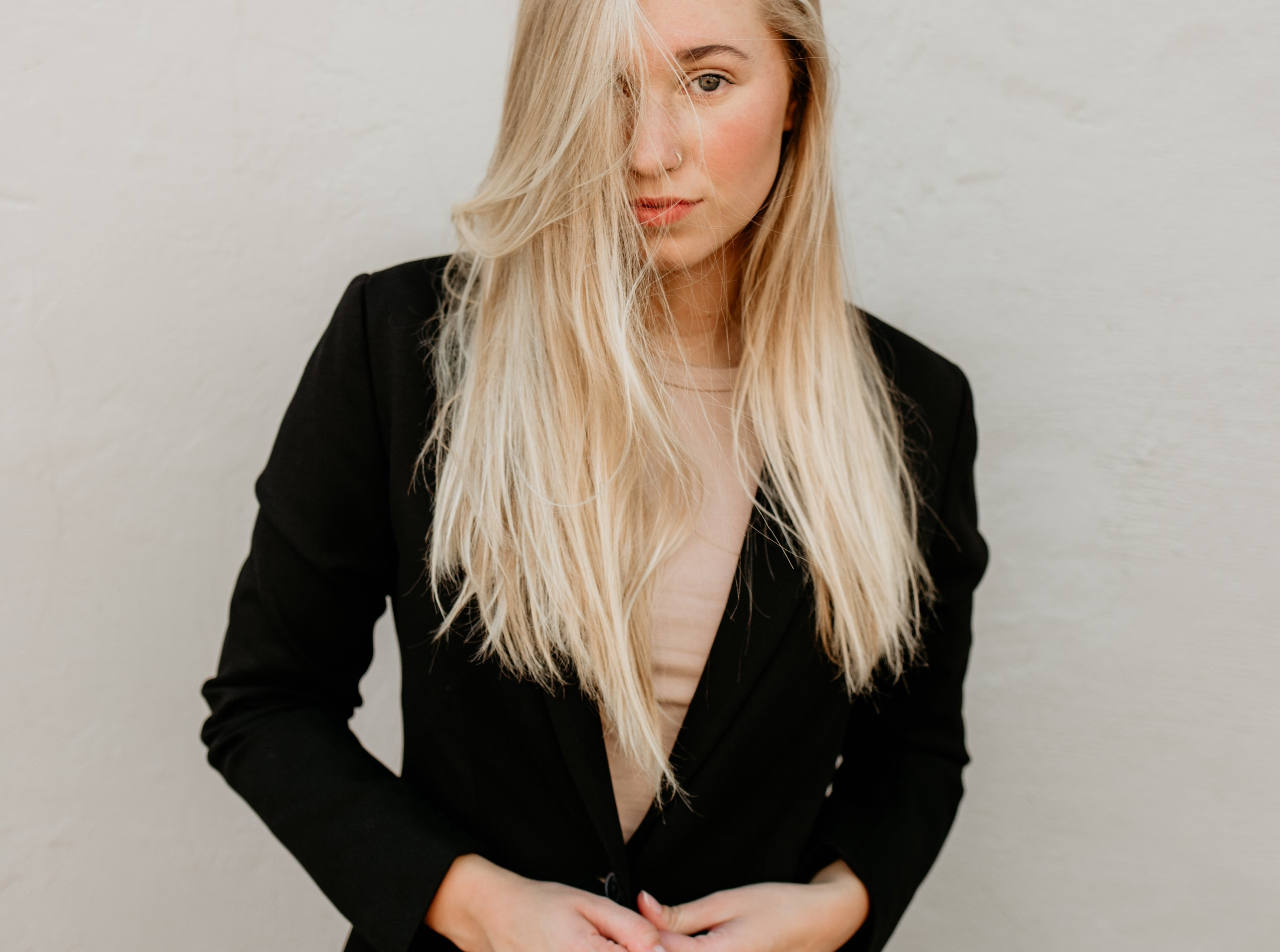 Person with long straight blonde hair, in a black suit jacket