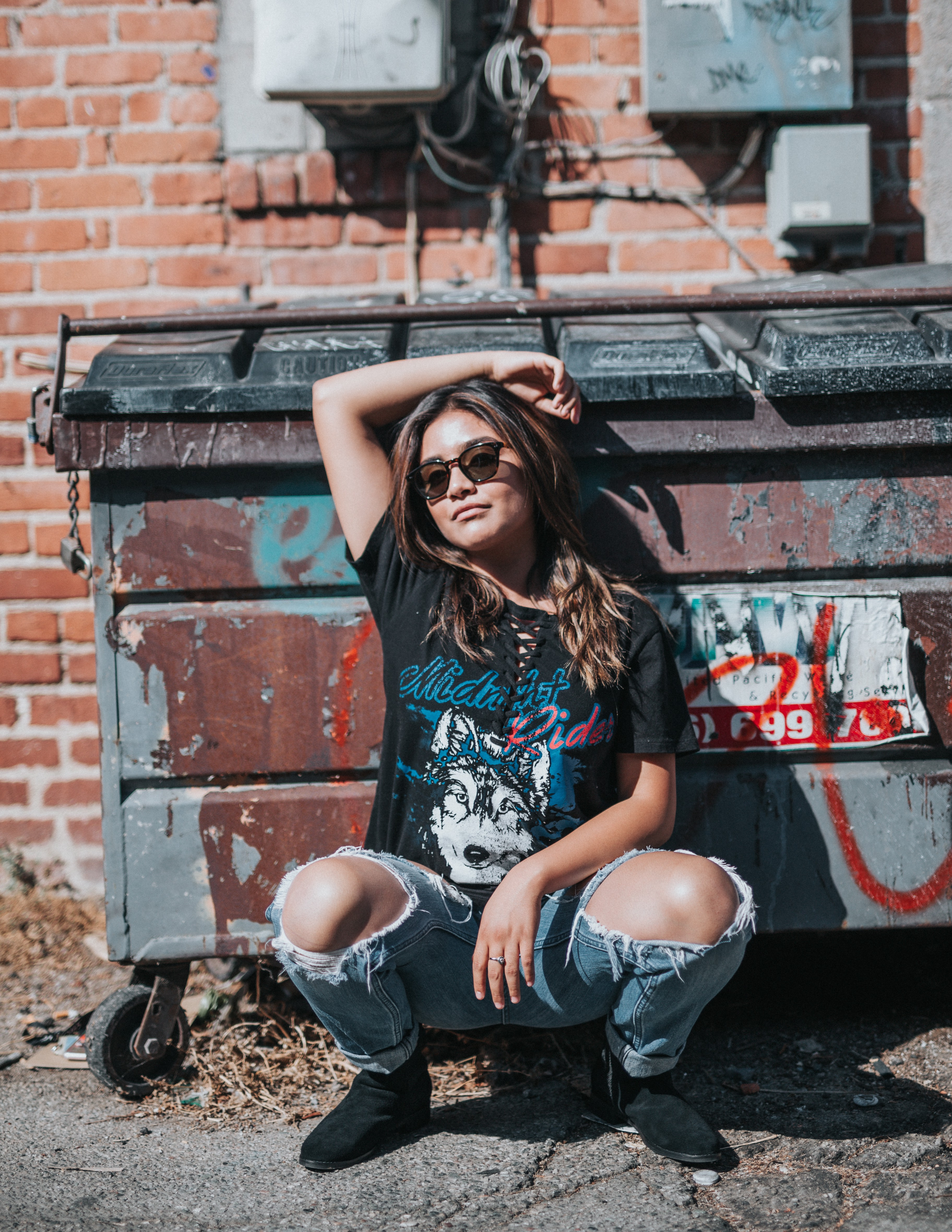 woman posing dramatically in front of a dumpster