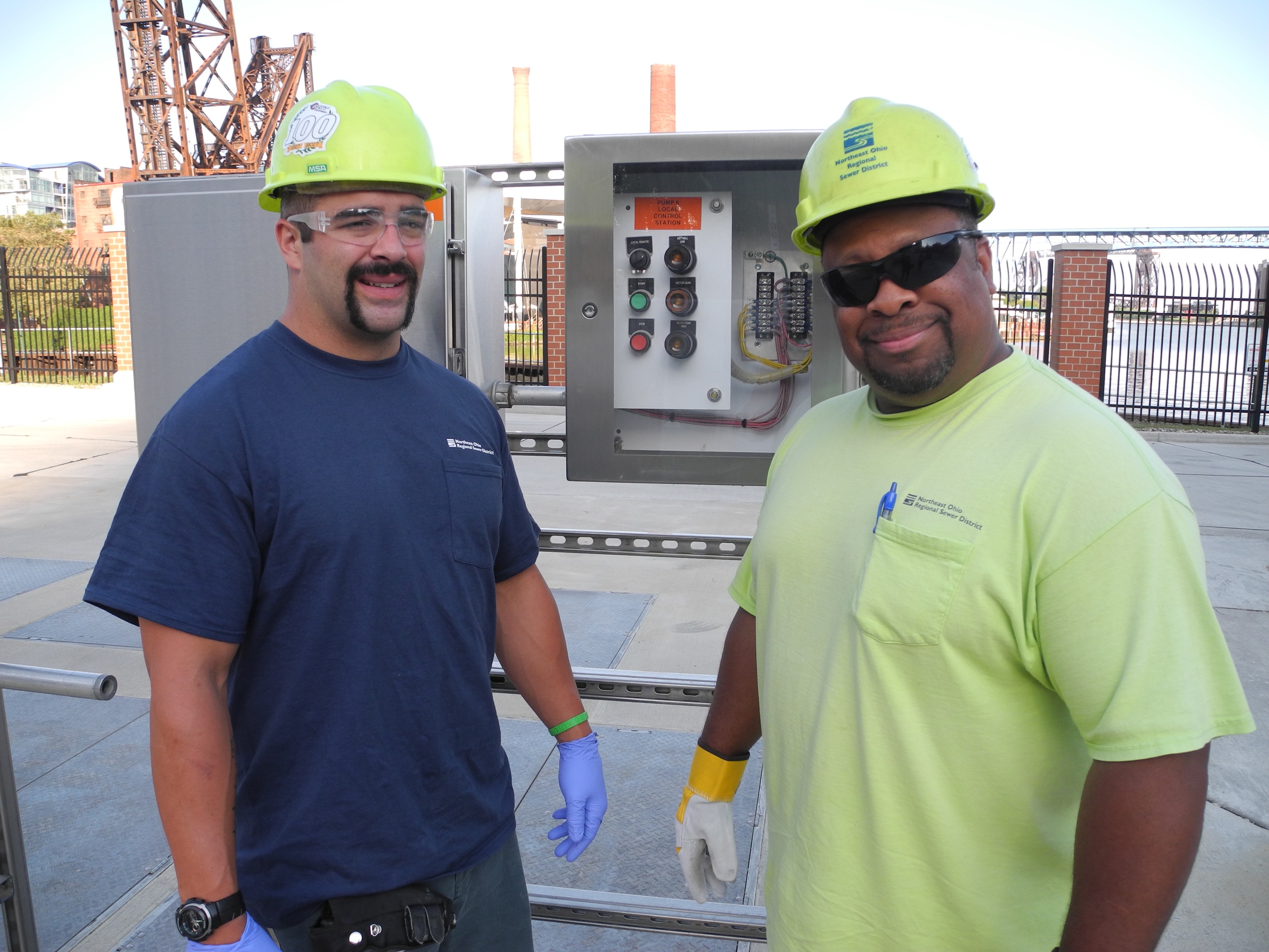 Two males stand in safety glasses and bright safety-yellow hard hats in front of a pump station electrical panel, smiling for the camera.