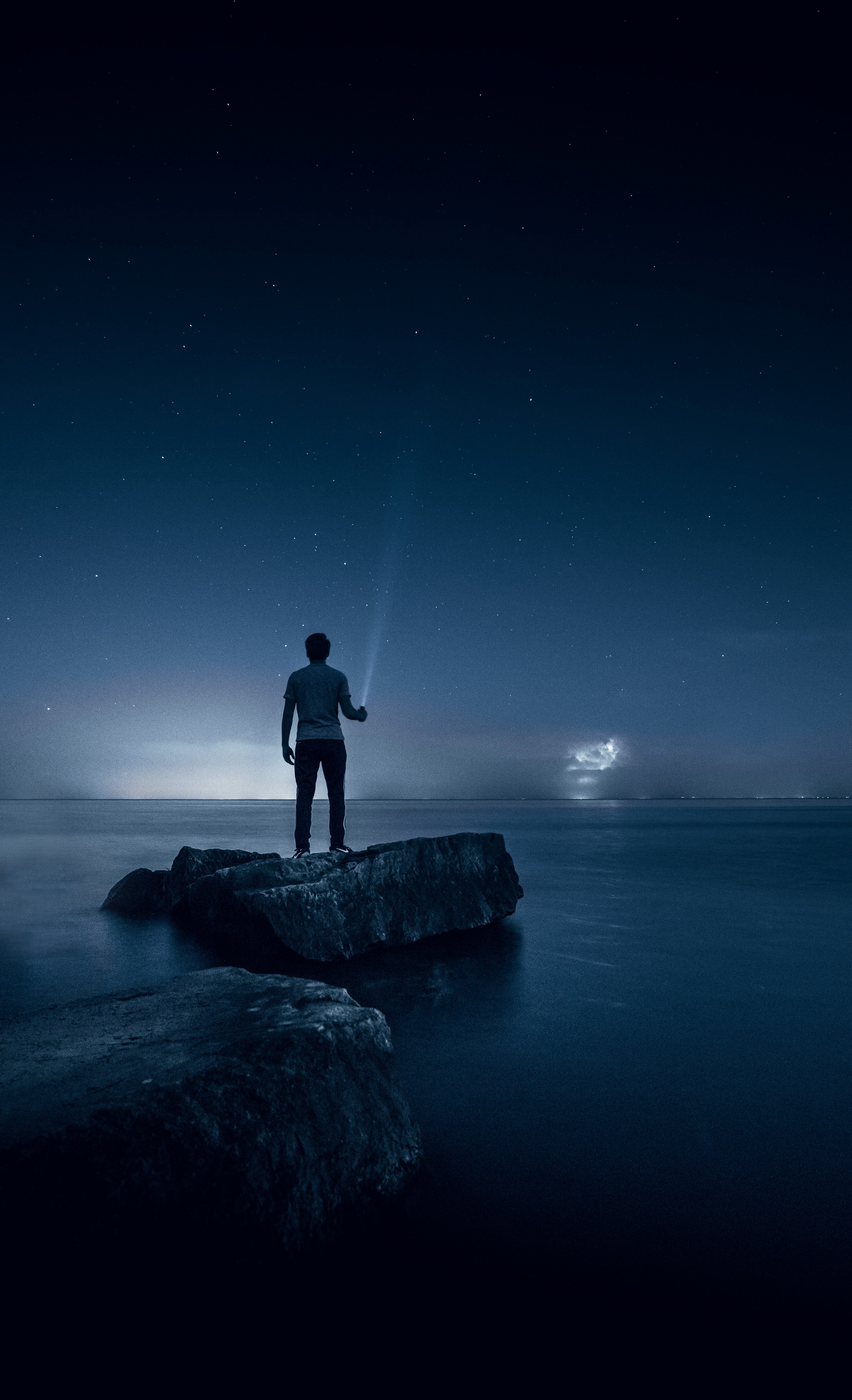 Man holding a torch looking at night sea