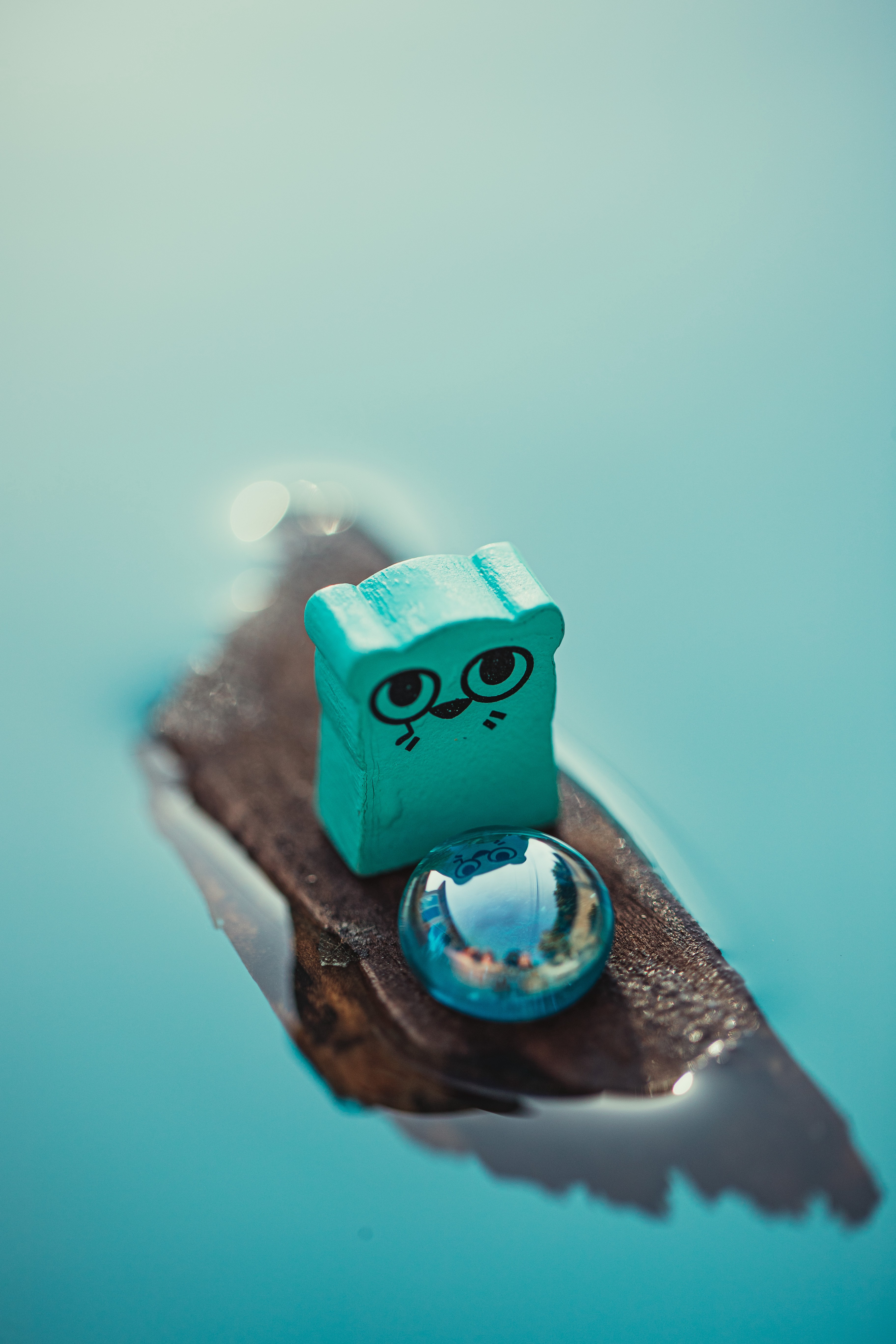 A teal, otter character meeple from the game Root floats on a wooden chip. I shiny blue marble sits in front on the otter.