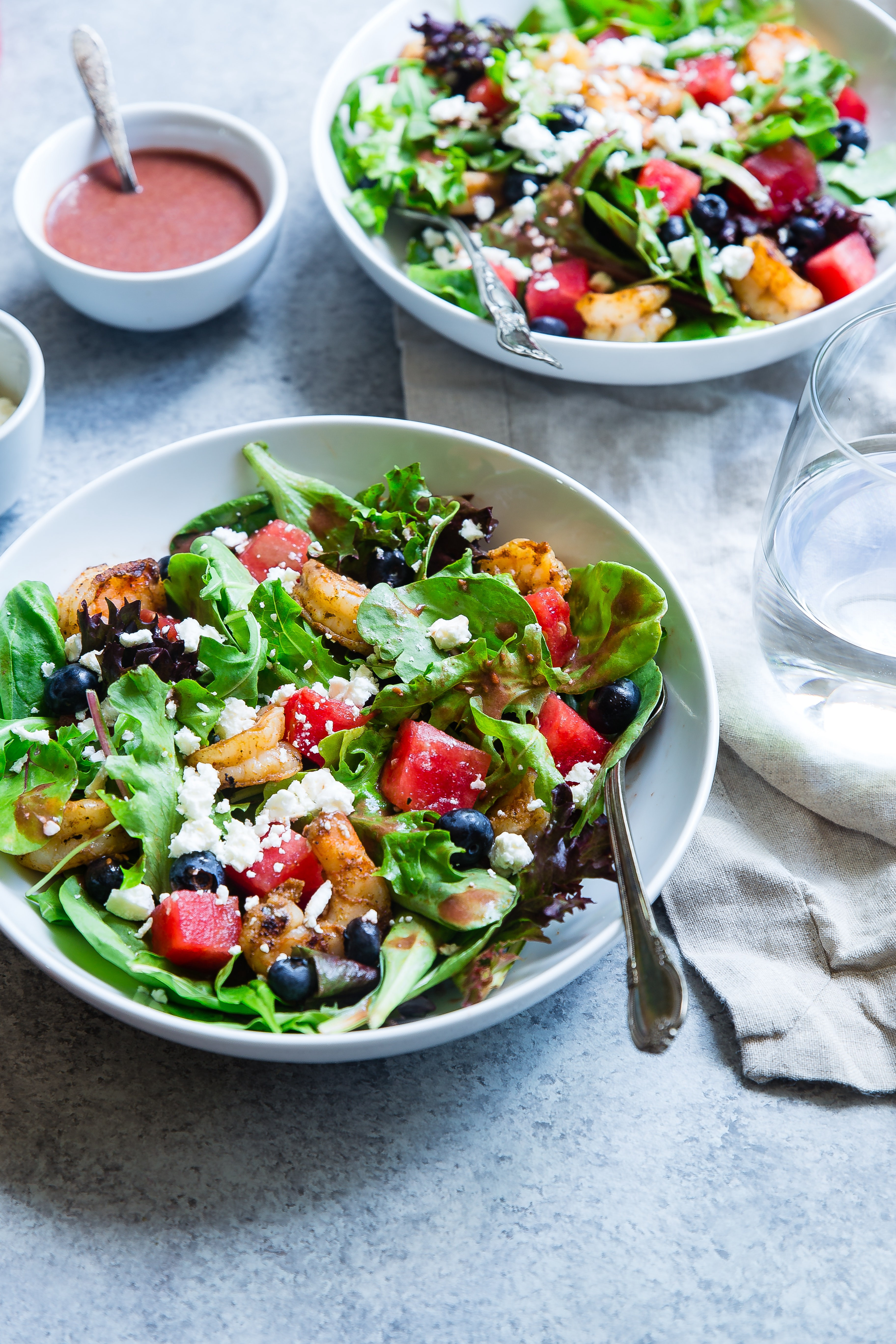 Picture of two bowls of colorful salads.