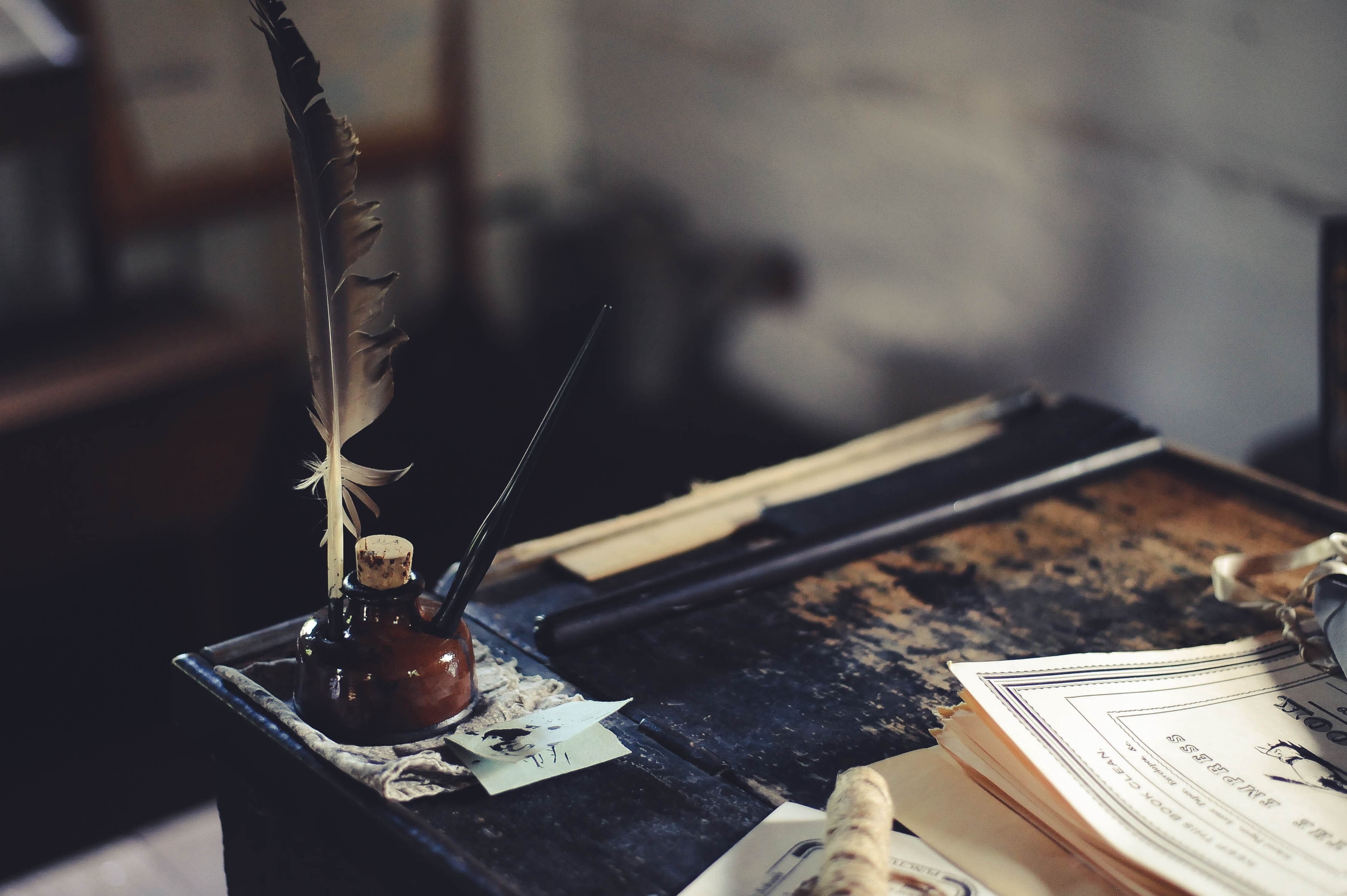 Old fashioned ink blotter and quill on the corner of an old desk with papers.