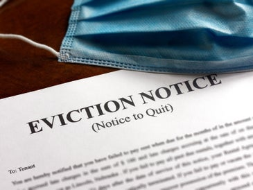A blue mask rests on top of an eviction notice