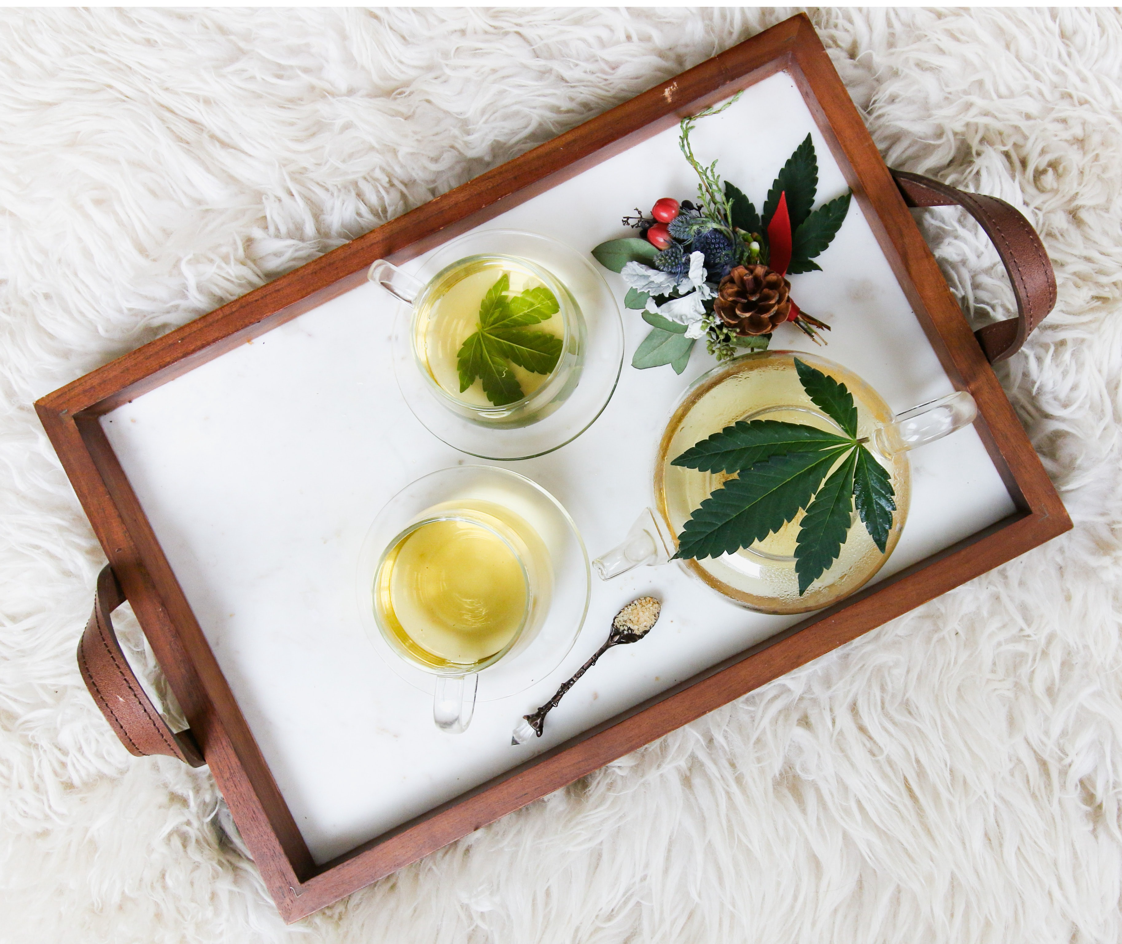 A tray shows tea with cannabis leaves in it.