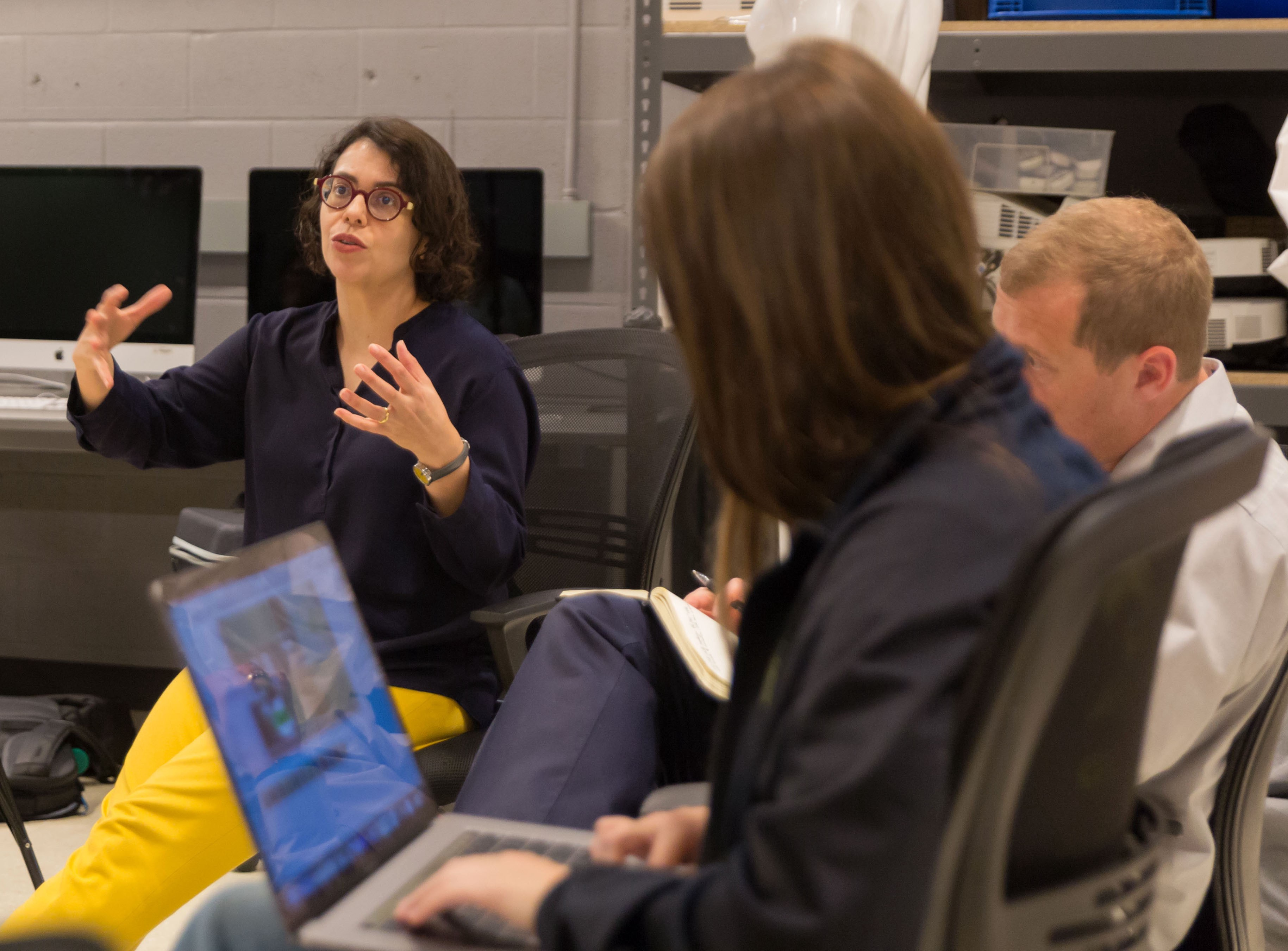 A UT engineering professor sits with fine arts and engineering students who are designing a virtual reality game about Texas.