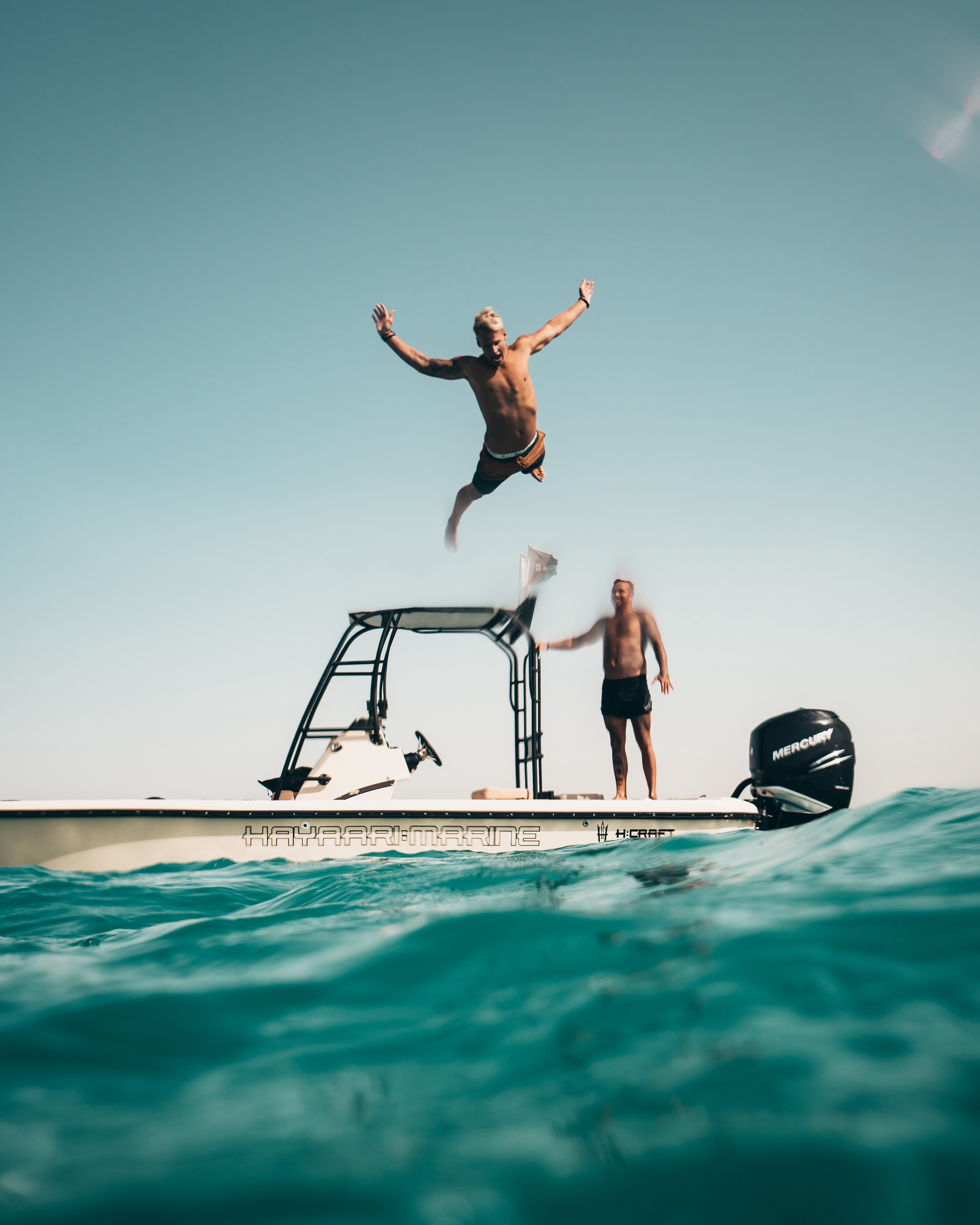 Photo of a man jumping off a small boat and who appears to be about to do a bellyflop into the water.
