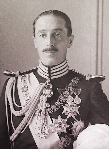 The Duke of Alba wearing a military uniform with many medals and decorations. He has short dark hair and a slim dark mustache