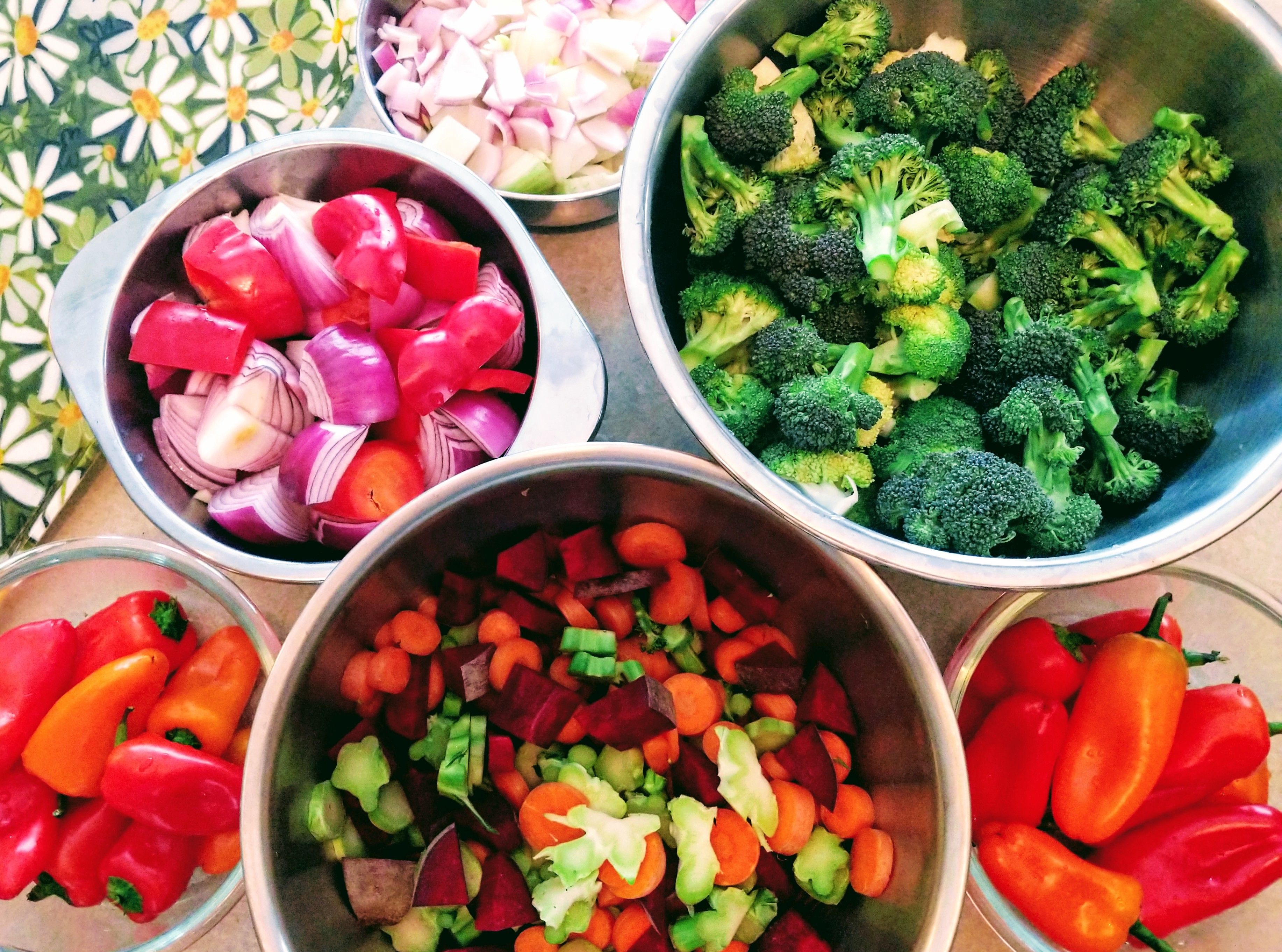 Glass and stainless steel bowls filled with fresh produce, including broccoli, red onions, carrots, beets, and sweet peppers.