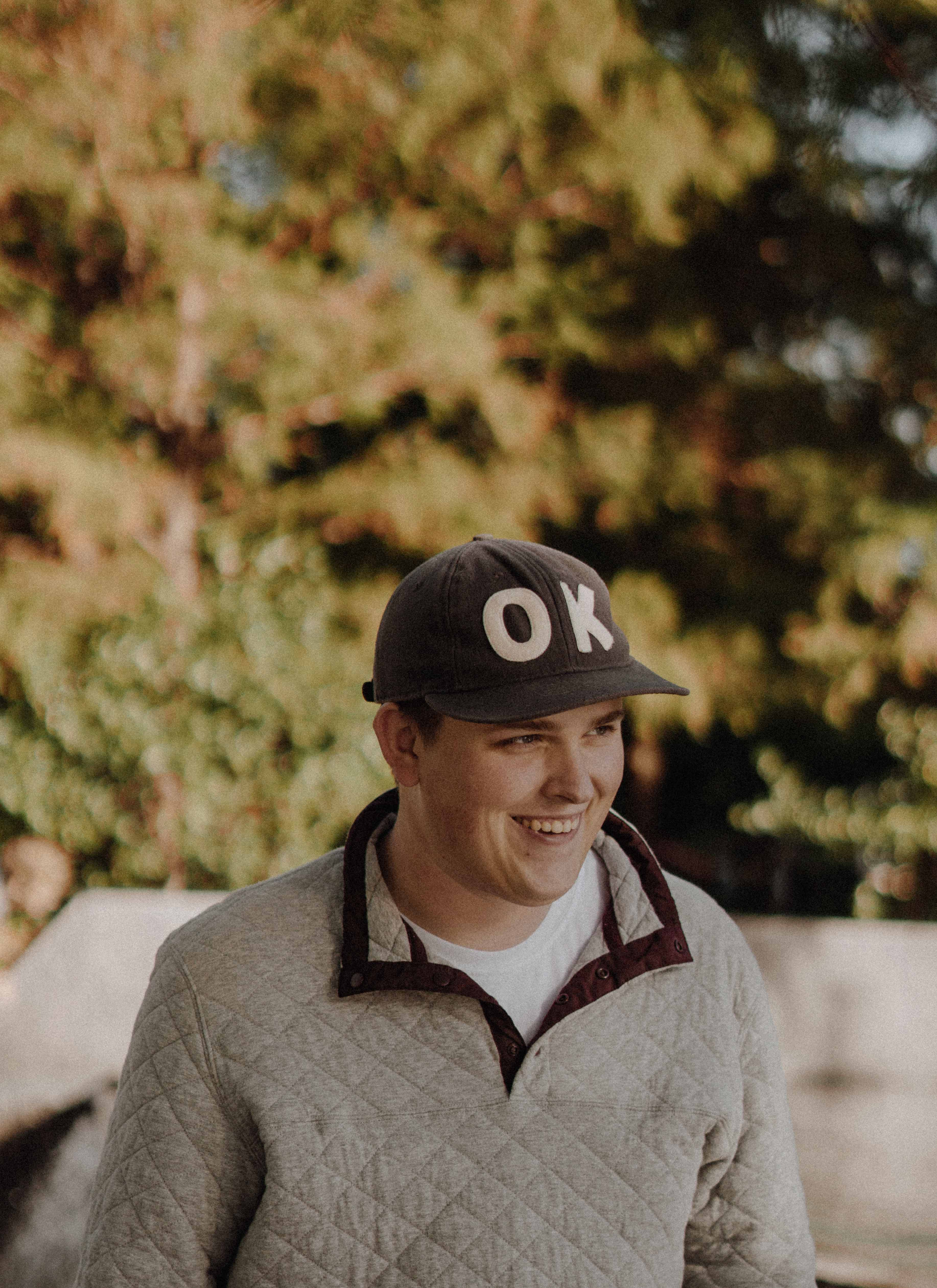 """Happy-go-lucky man with """"OK"""" on his hat"""