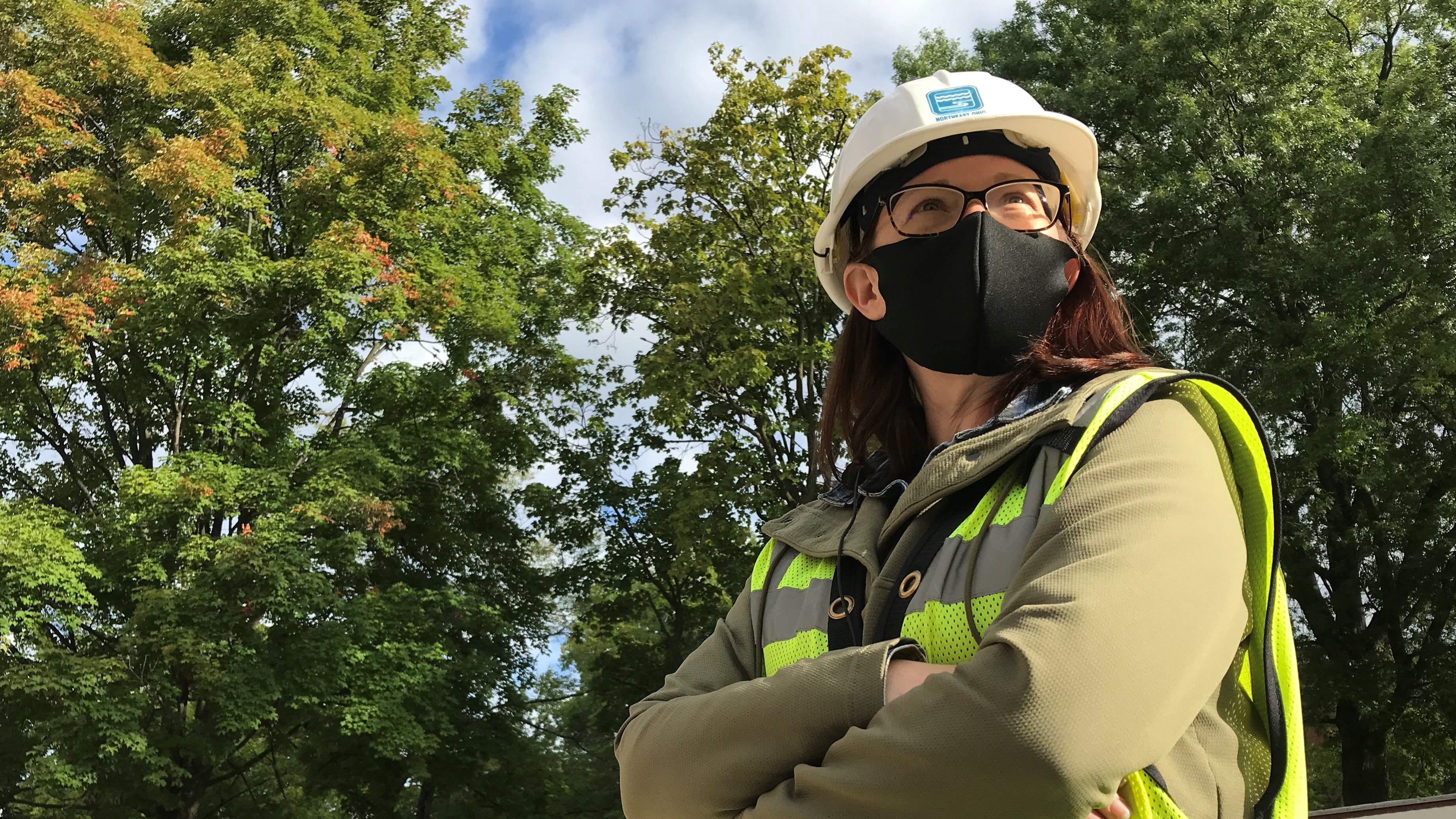 Female construction supervisor in a face covering, safety vest, and hard hat. Arms folded, focused on a point beyond the camera as she overlooks a project site on a sunny fall day in Cleveland.