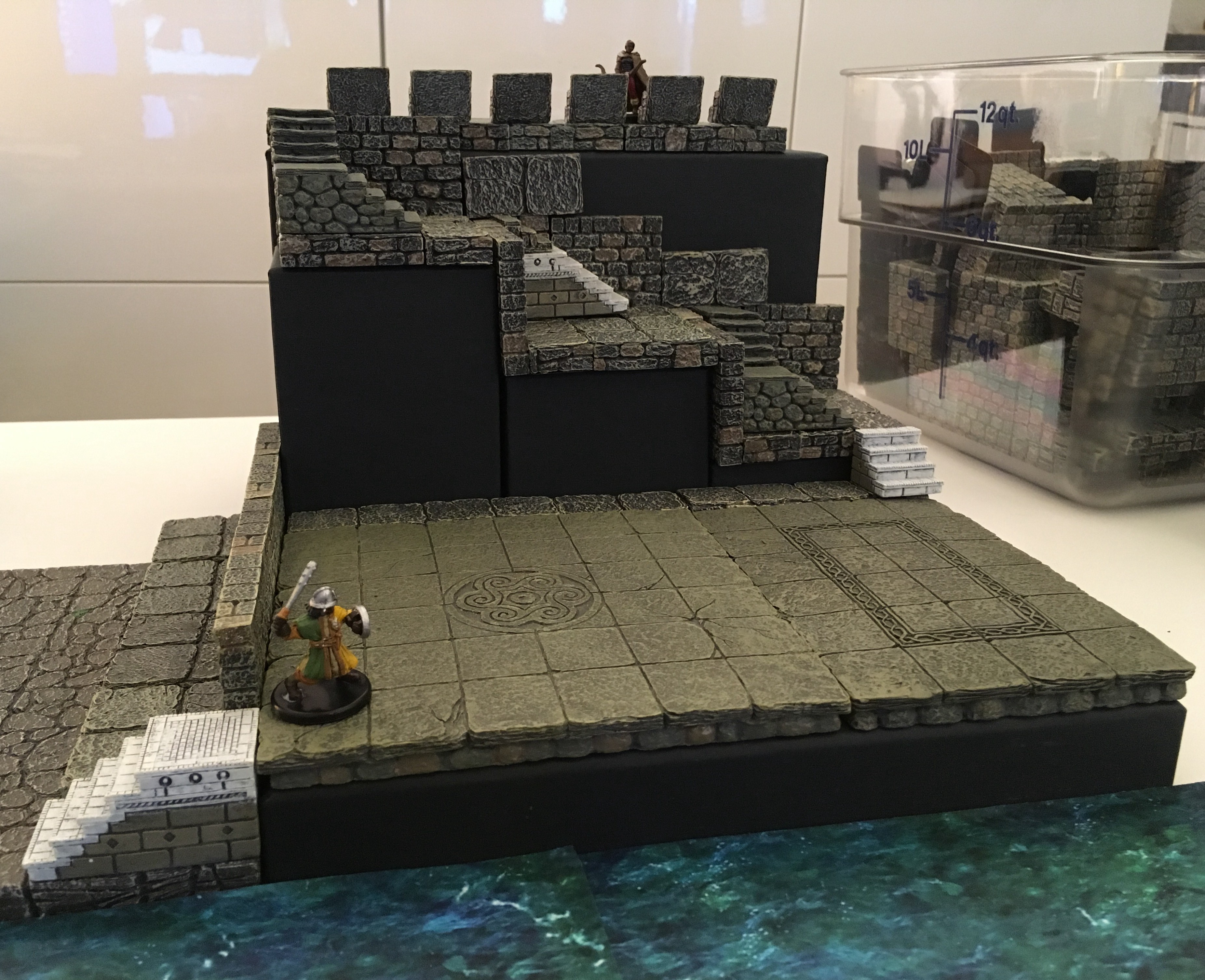 A miniature fighter advances across a raised courtyard, as 4 levels up an archer watches. Underneath it all: black boxes.