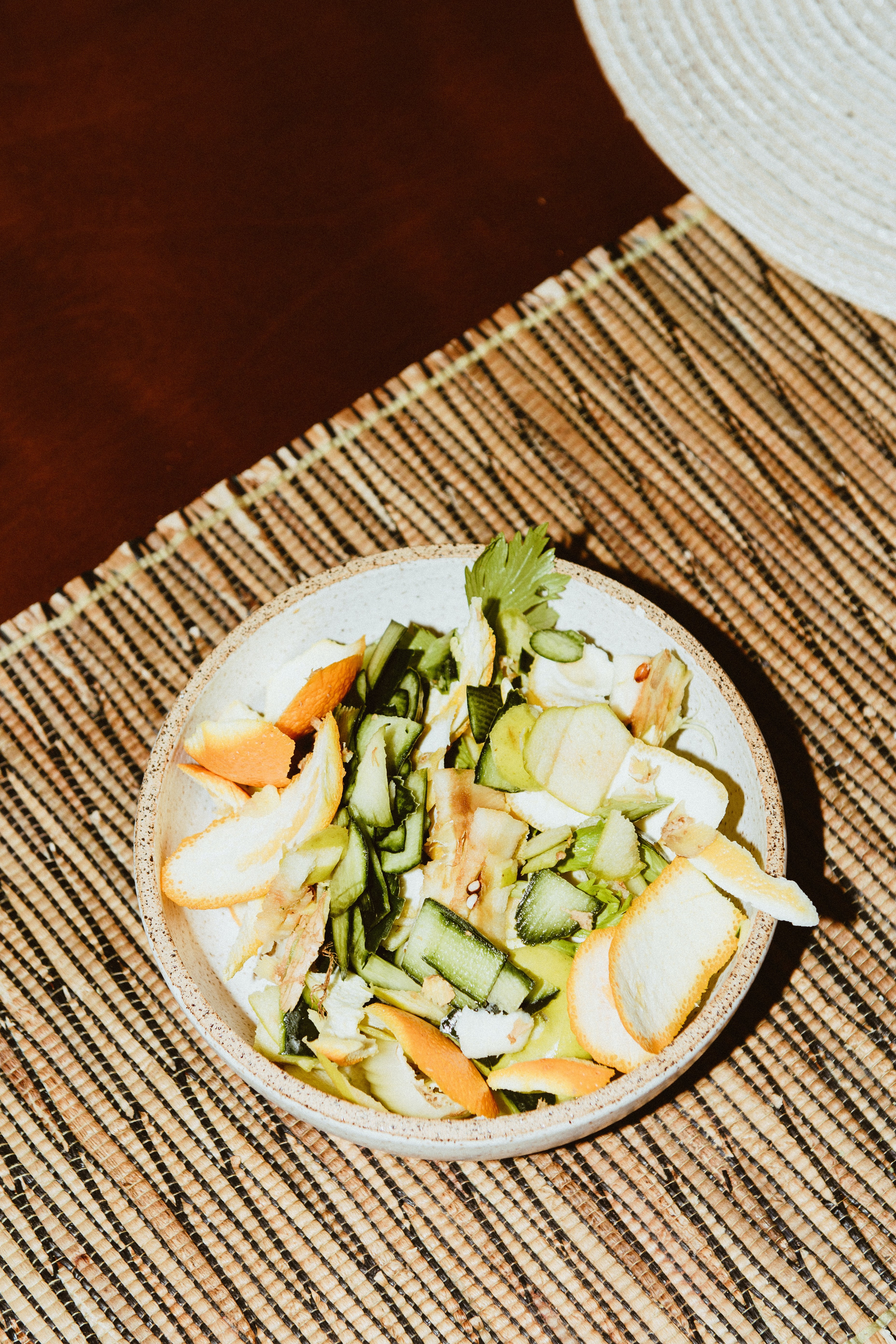 A bowl of food scraps—orange peels, cucumbers, and lettuce—atop a wood placemat.