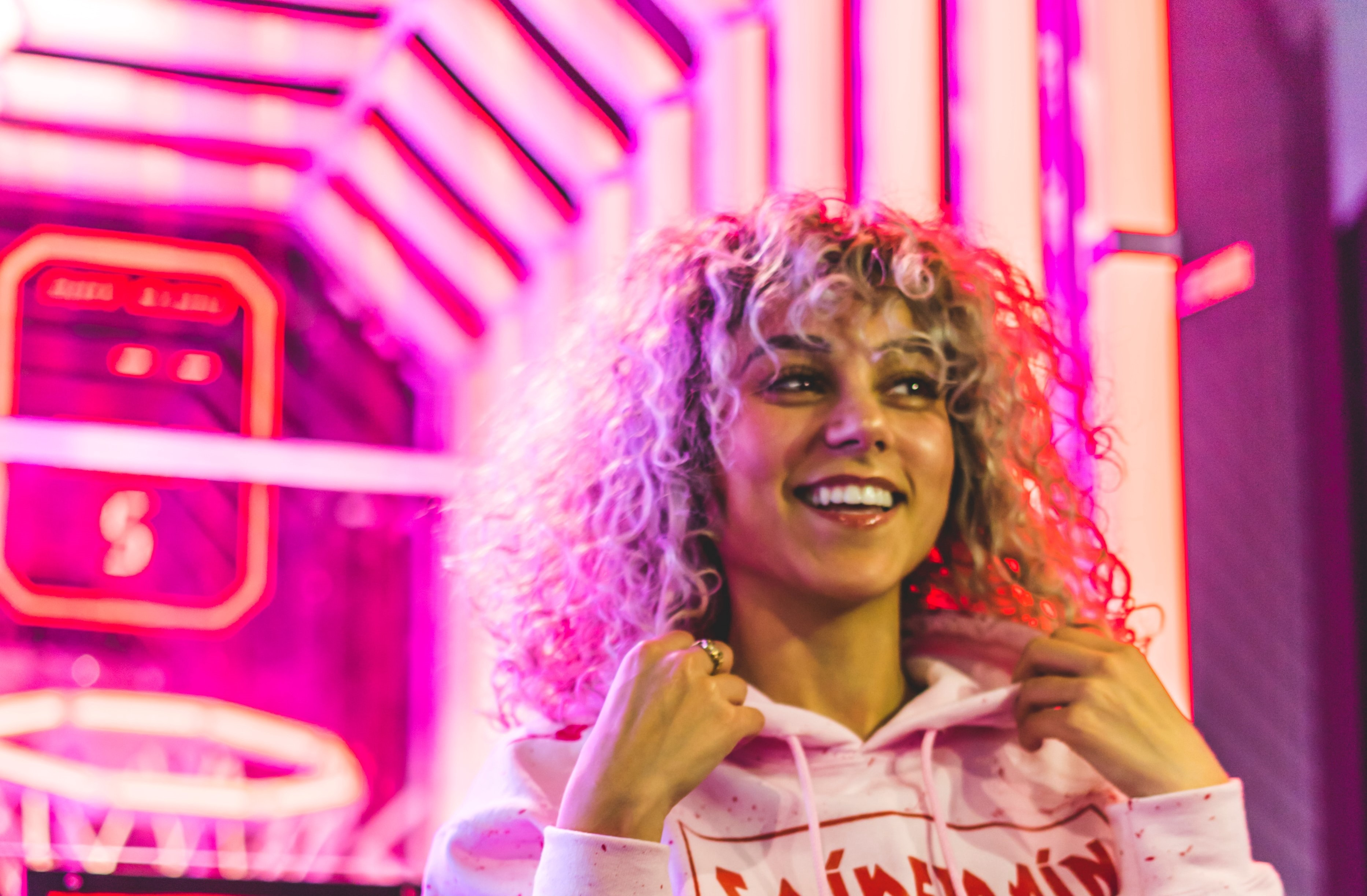 Curly-haired person in a hoodie smiling, lit up by pink arcade lights