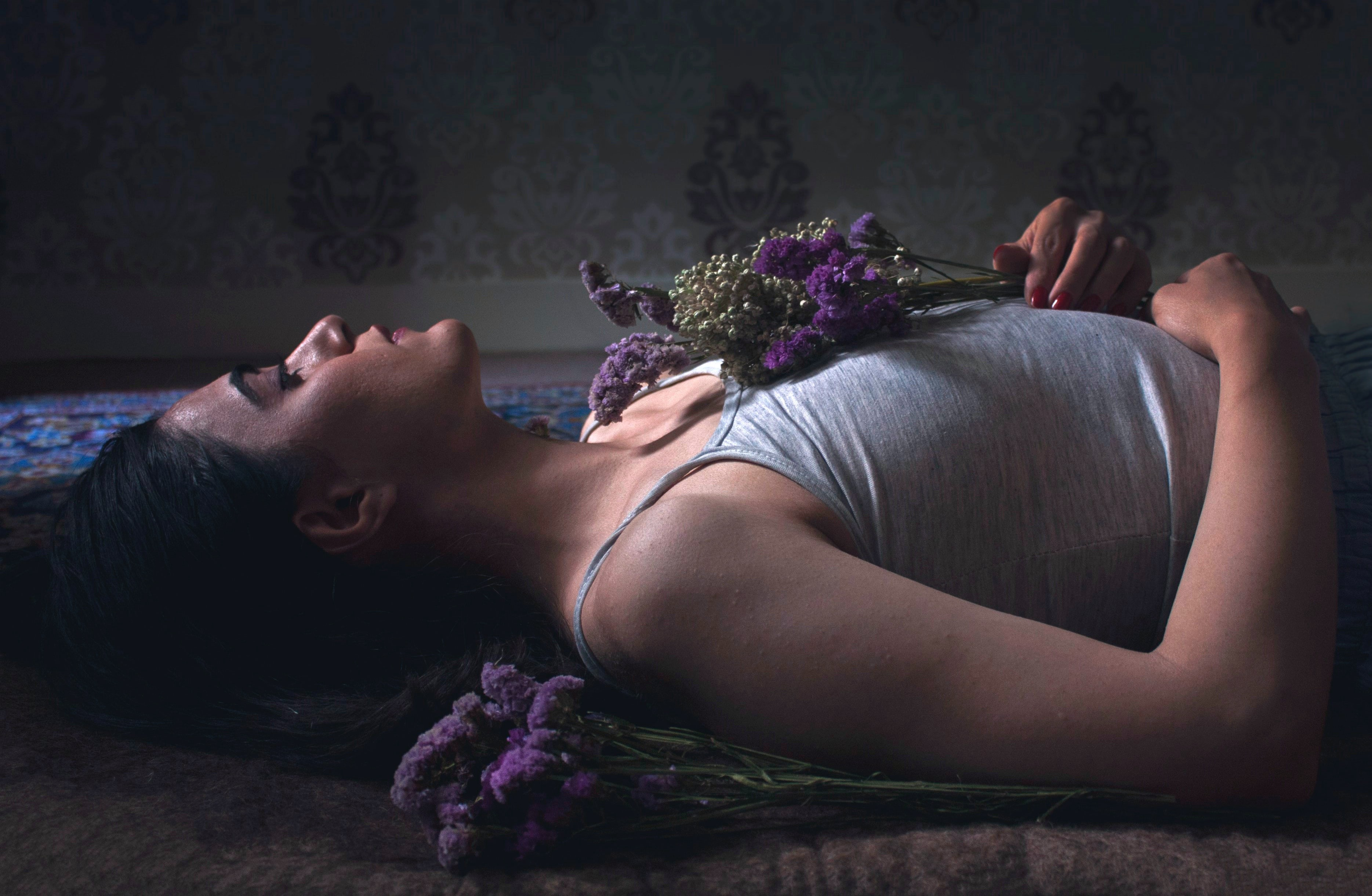 Young woman holding flowers while lying on the floor